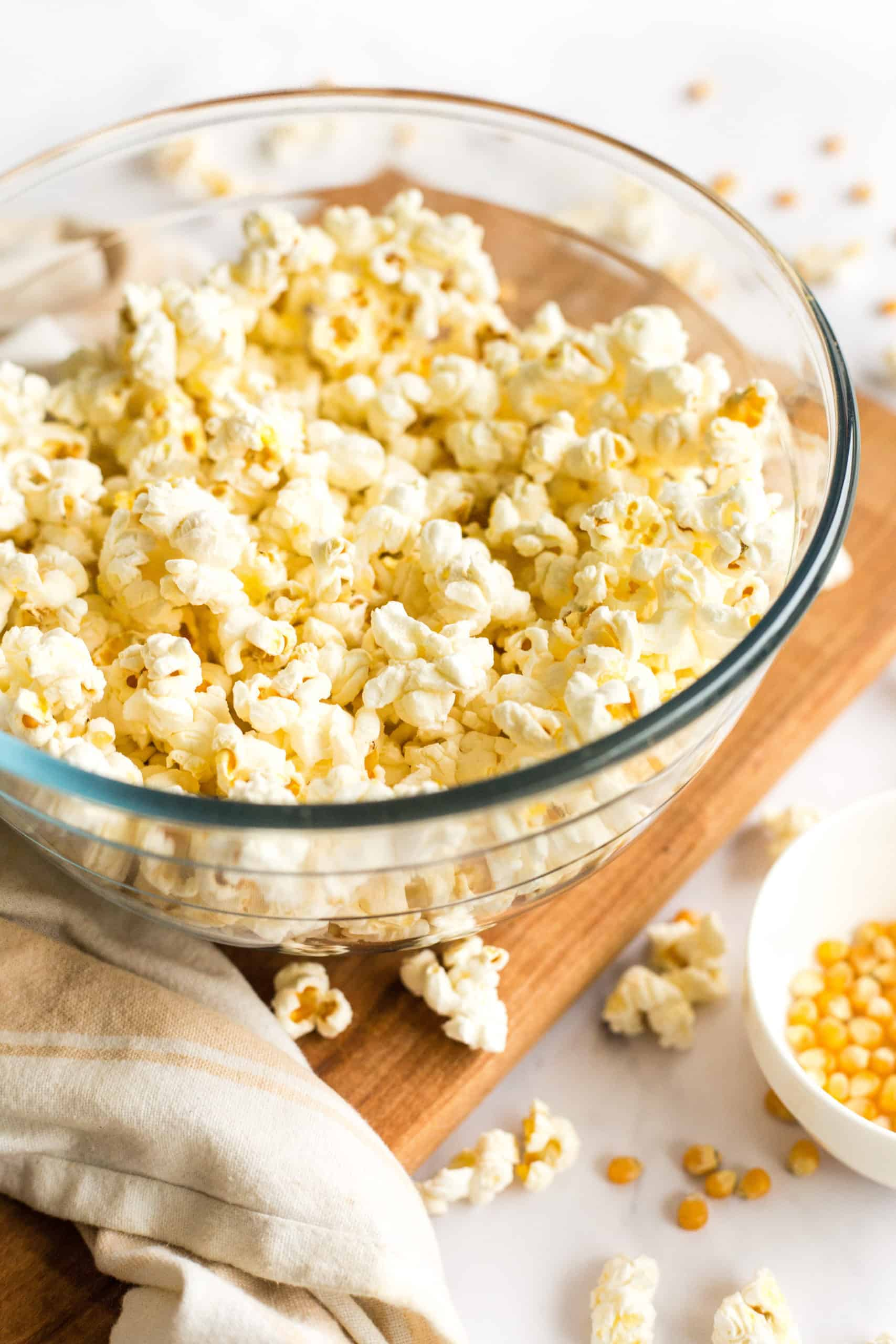 Freshly made popcorn in a glass bowl on a wooden board.
