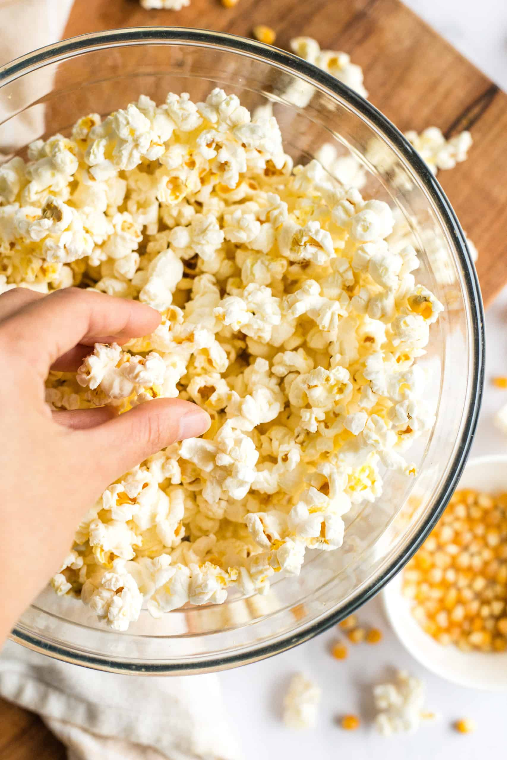 Freshly popped popcorn in a glass bowl.