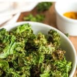 Kale chips in a bowl on a wooden board