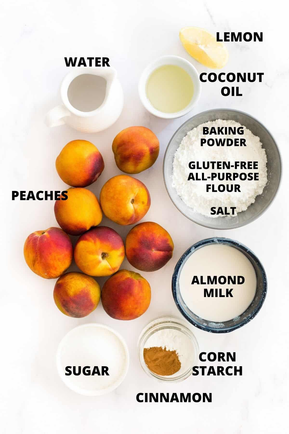 Ingredients for making peach cobbler laid out on marble board.