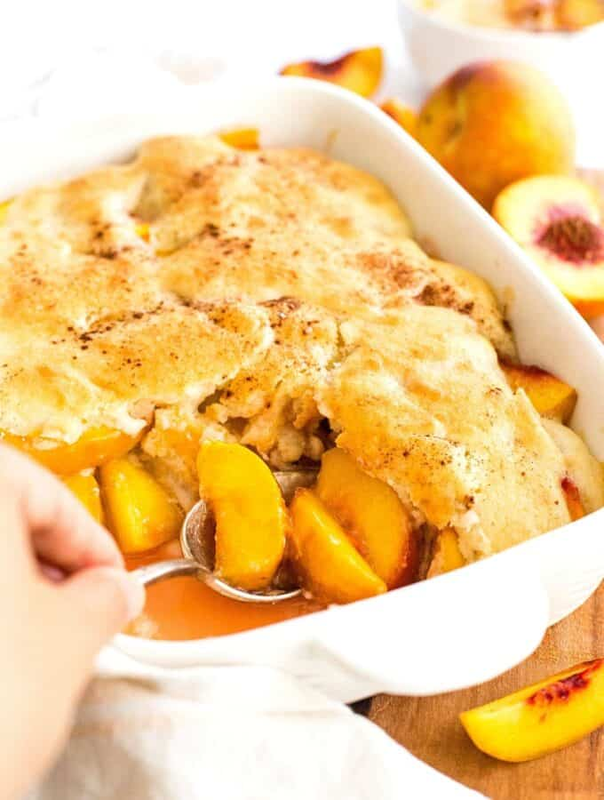Scooping peach cobbler from casserole dish.