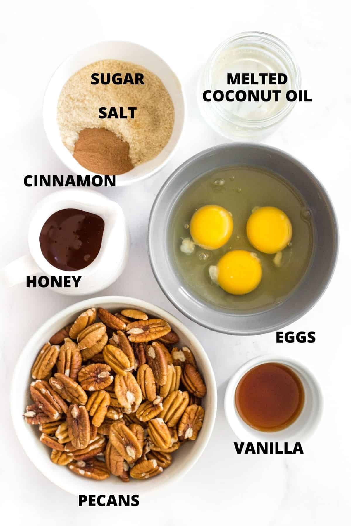 Labeled ingredients for pecan pie filling laid out on marble board.