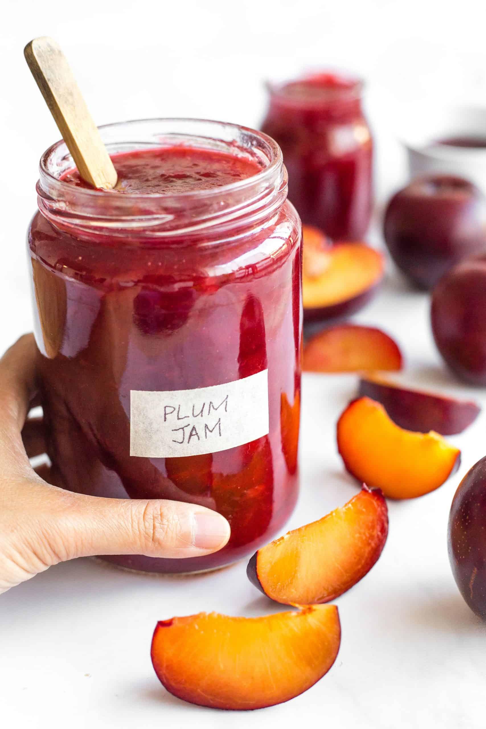 Hand holding a jar of plum jam