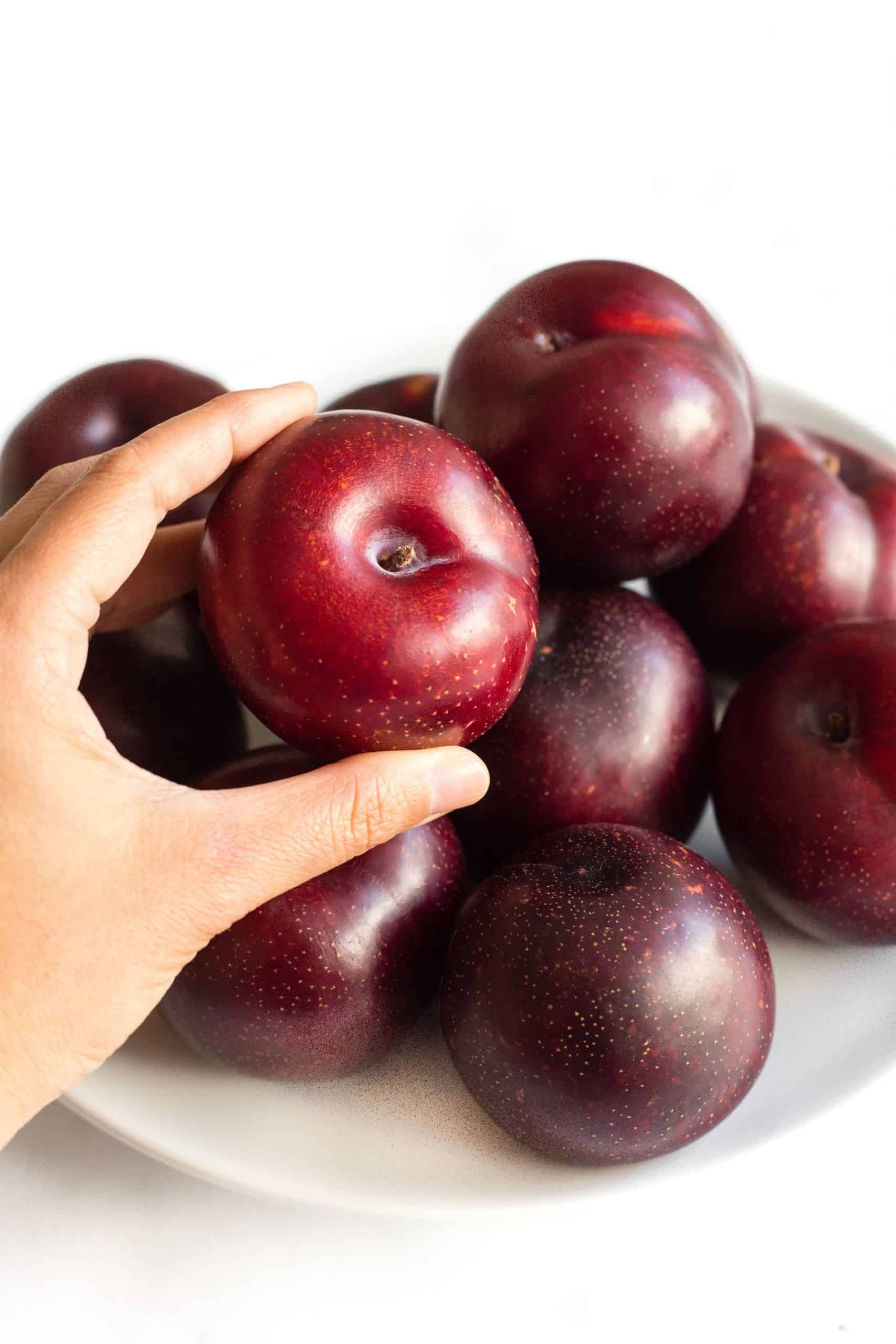 Hand reaching for a fresh plum from a plate full of plums.