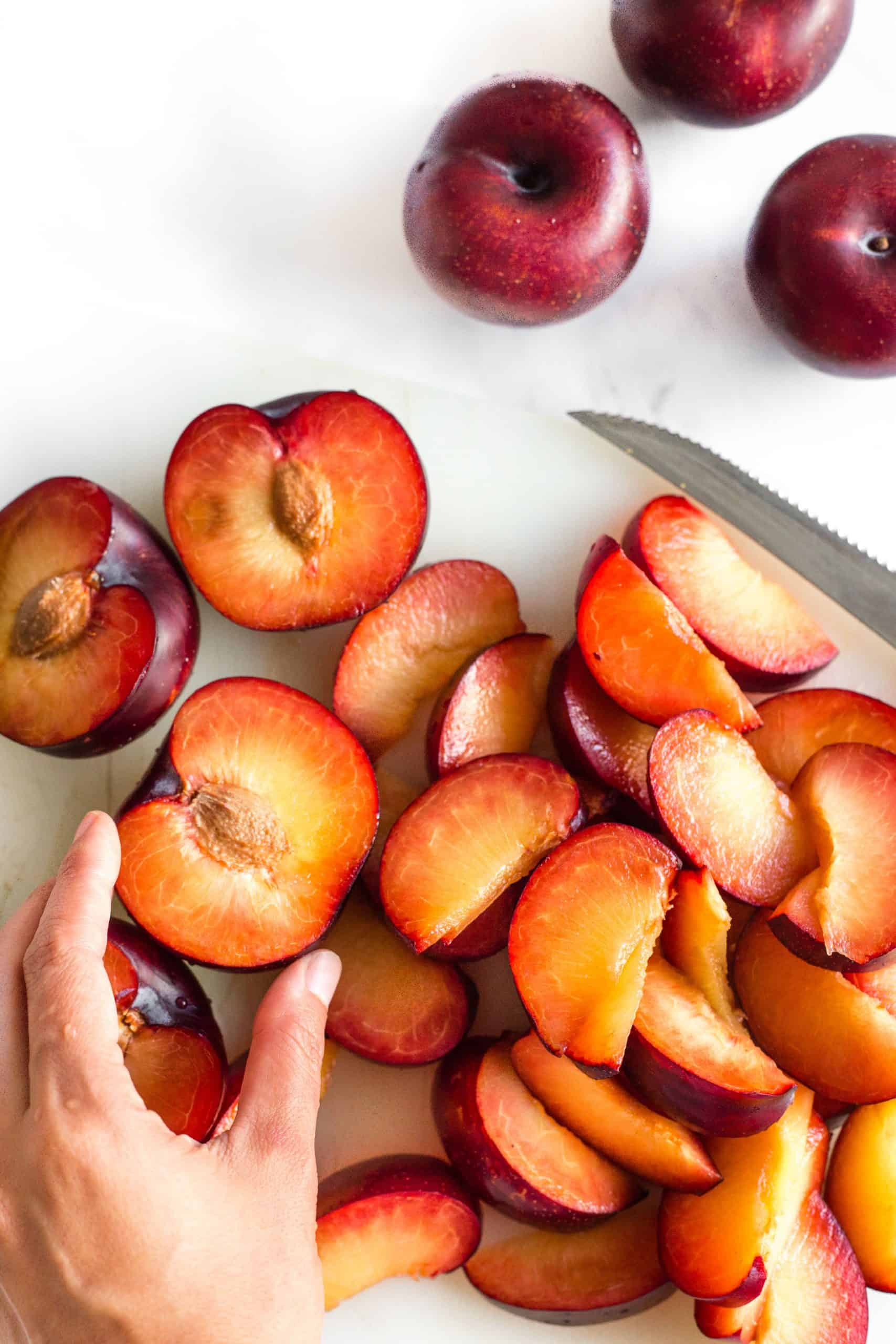 Sliced plums on a chopping board.