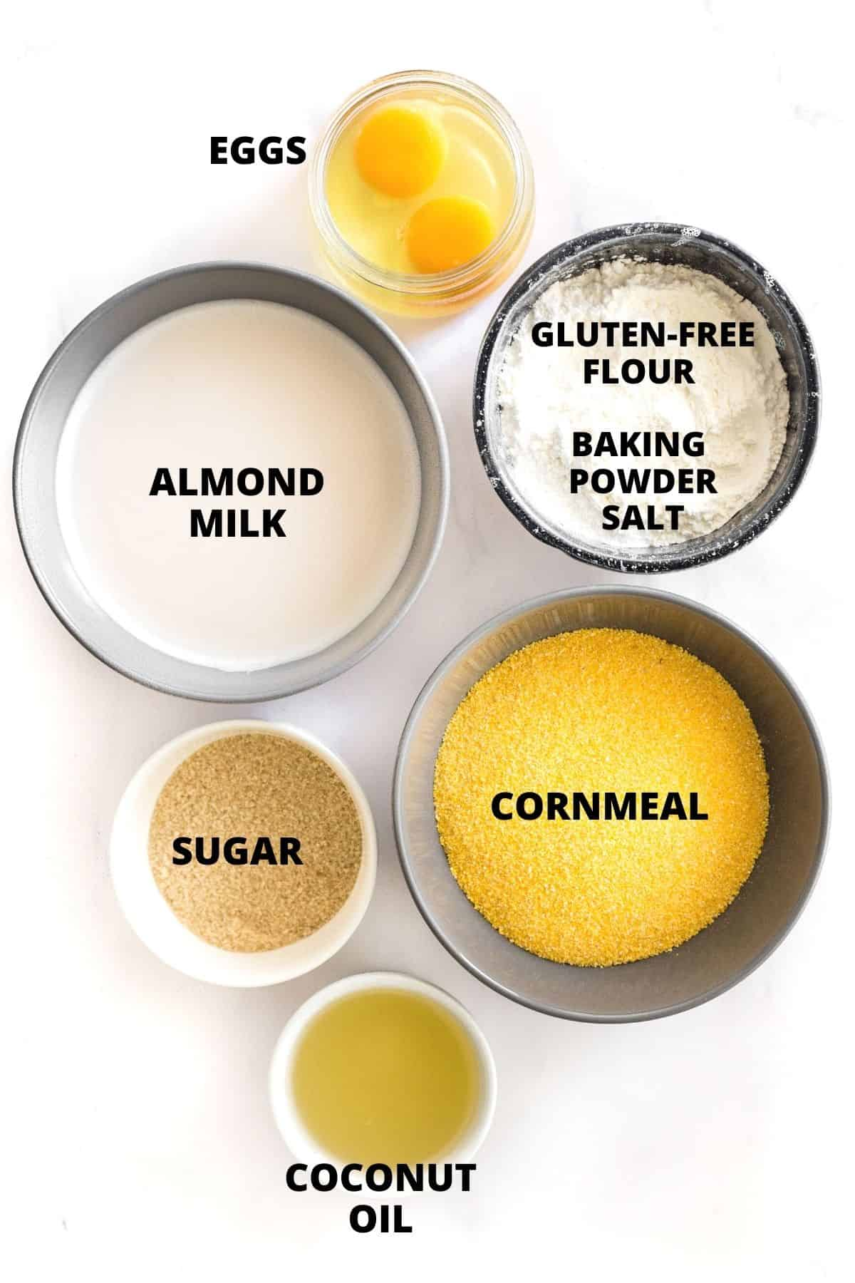 Labeled ingredients for gluten-free cornbread laid out on marble board.