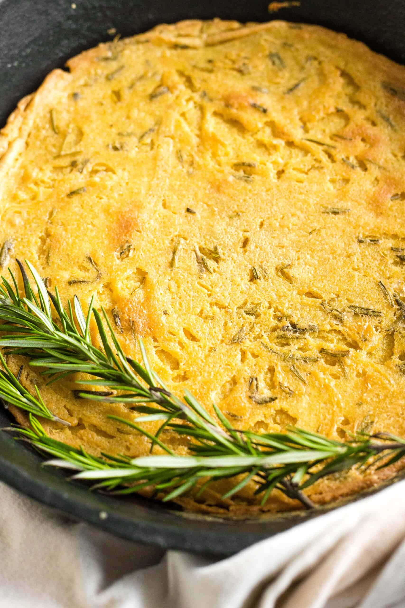 Fresh rosemary on top of a skillet of farinata.