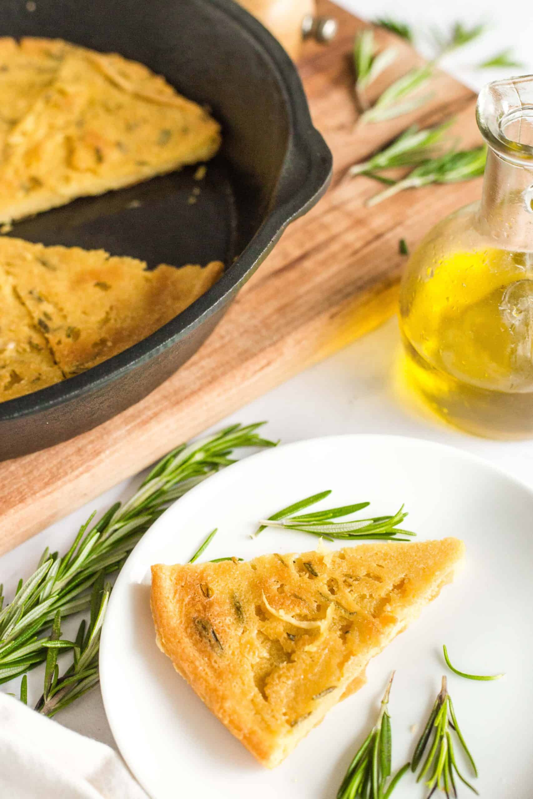 A slice of chickpea flatbread and fresh rosemary leaves on a small plate.