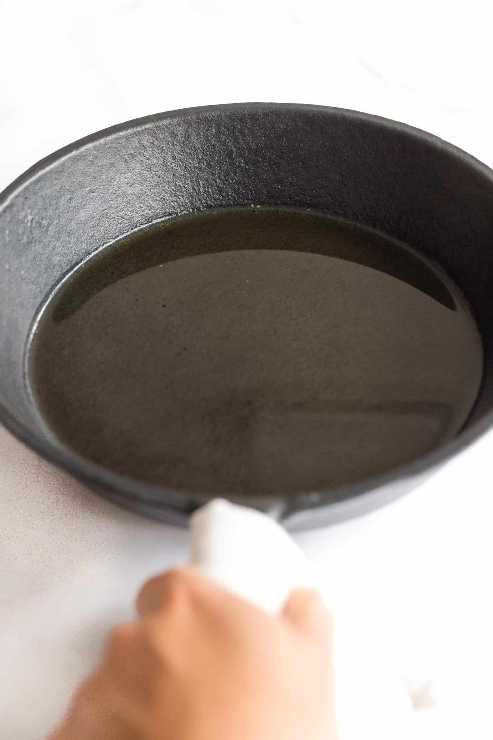 Holding a cast iron skillet with oil.