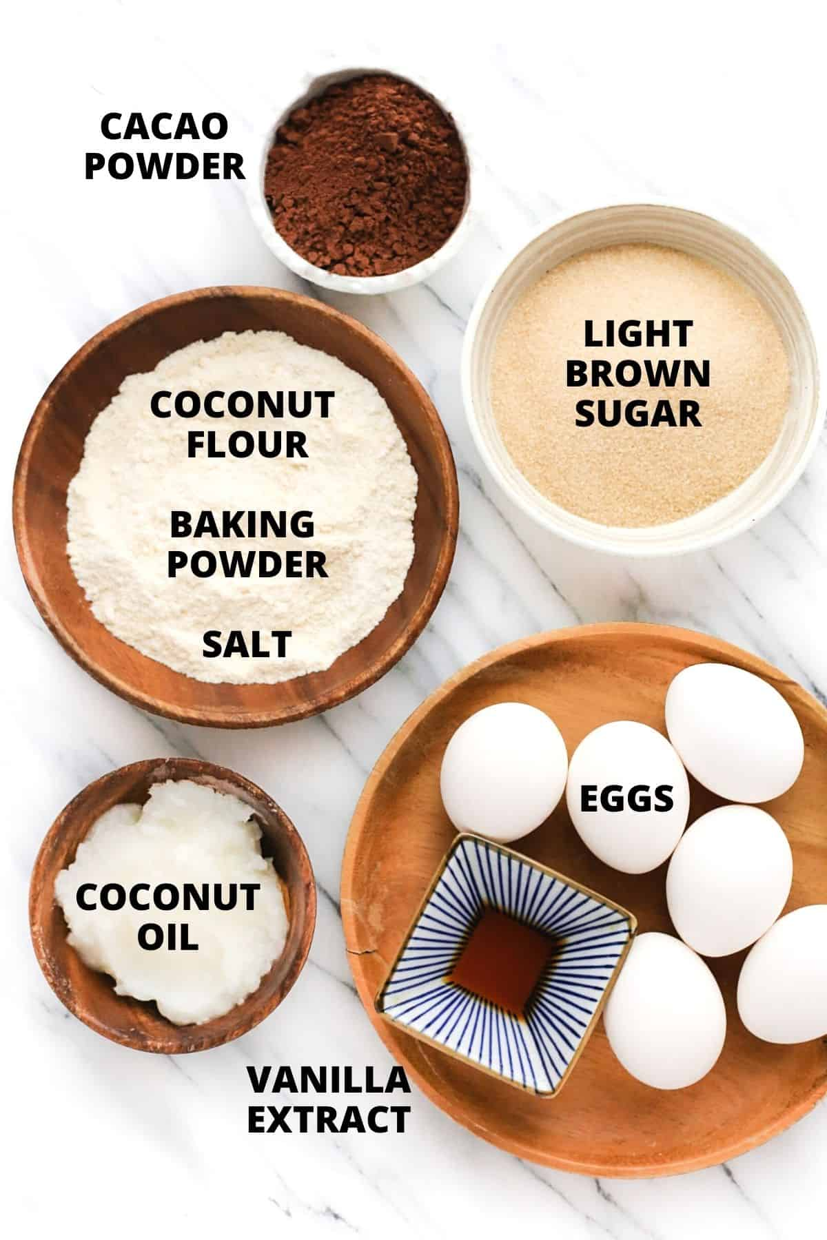 Labeled ingredients for flourless chocolate cake set out on a marble board.