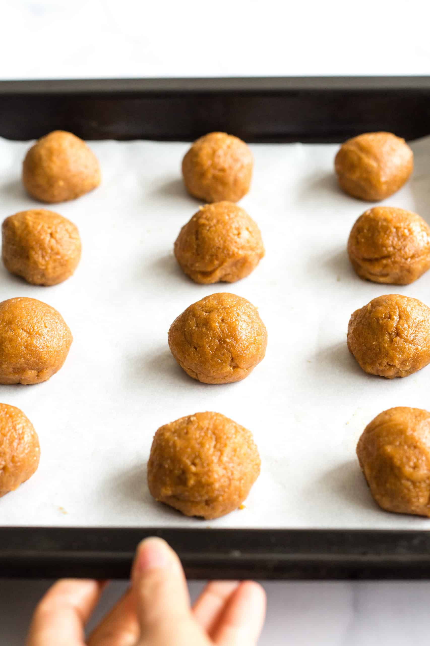 Peanut butter cookie dough balls lined up on a parchment-lined baking sheet.