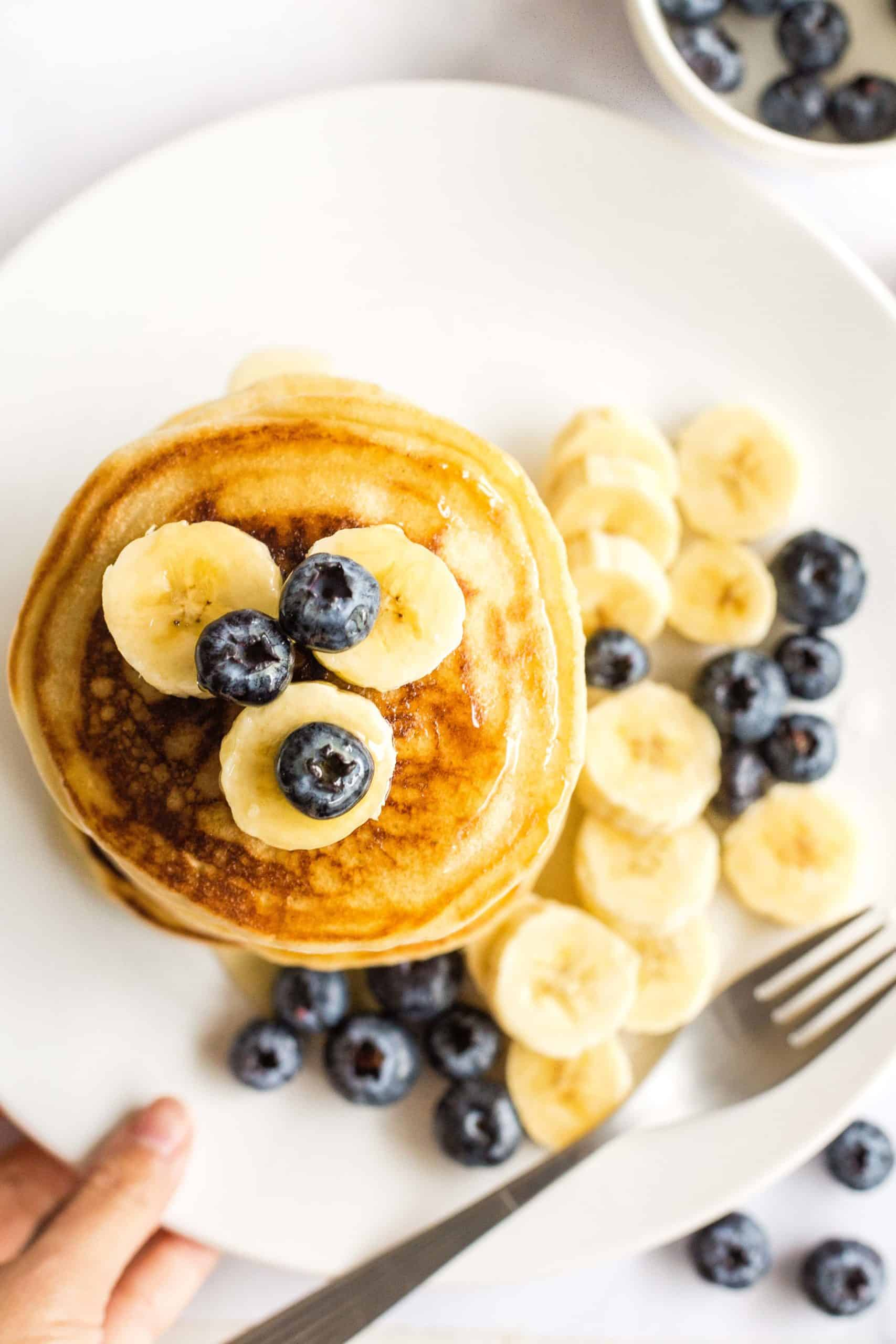 Gluten-free pancakes topped with blueberries on a plate.