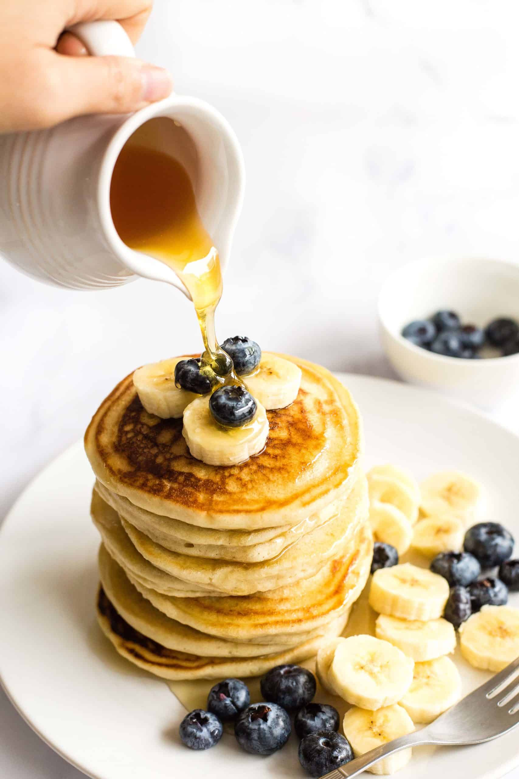 Hand pouring maple syrup over a stack of fluffy gluten-free pancakes.