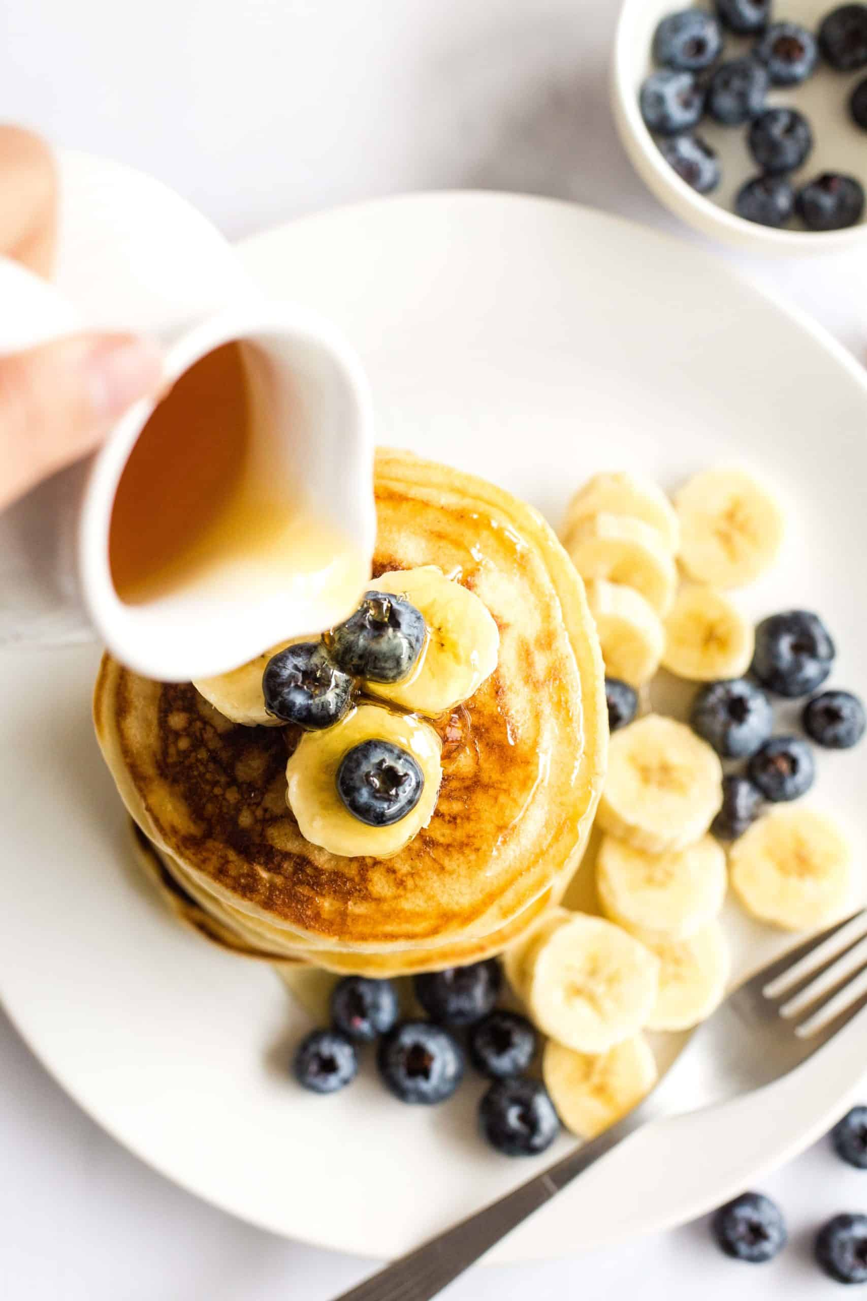 A hand pouring maple syrup onto a stack of gluten-free pancakes.