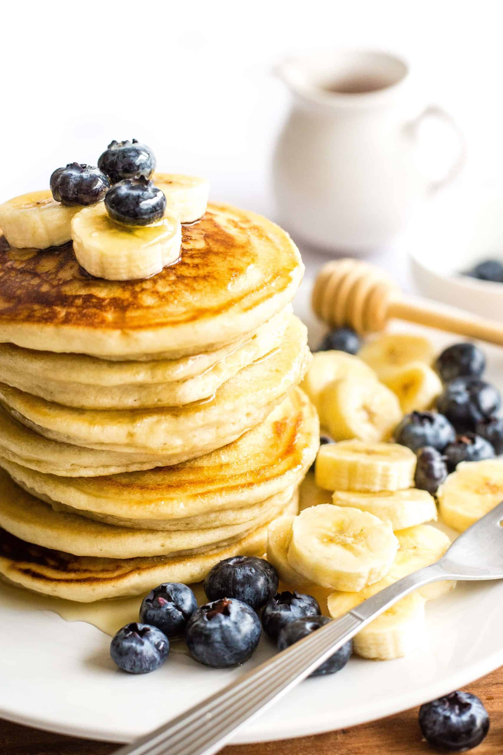 A stack of gluten-free pancakes topped with blueberries and sliced bananas on a plate.