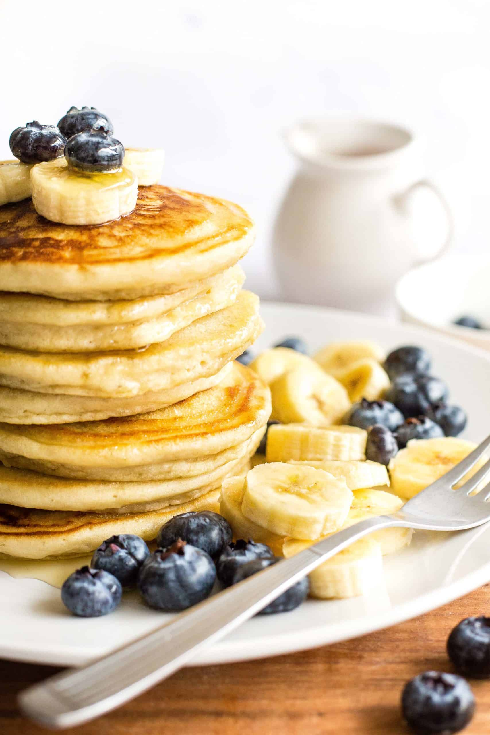 A tall stack of fluffy gluten-free pancakes topped with fruit and drizzled in maple syrup.
