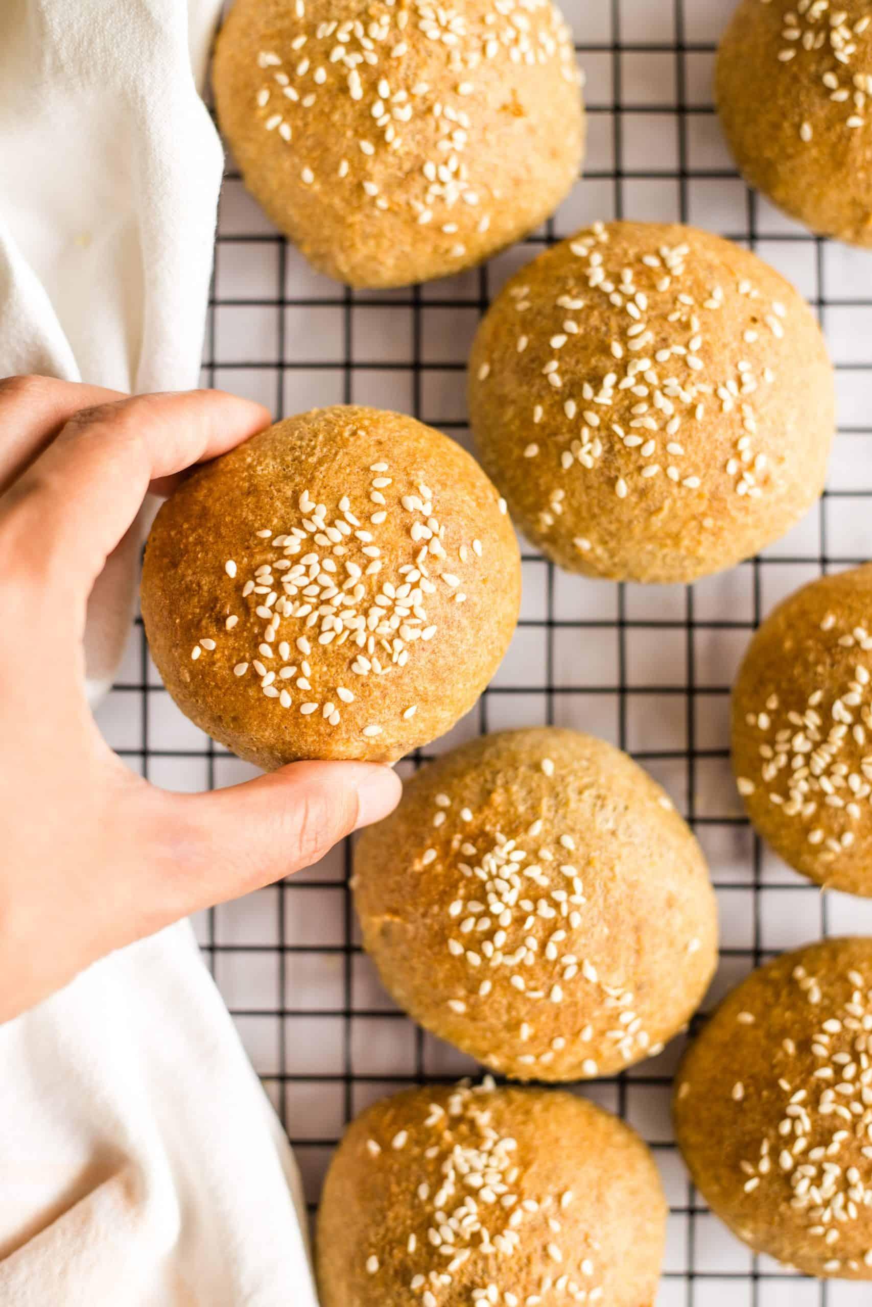 Hand holding up a gluten-free sesame bun.