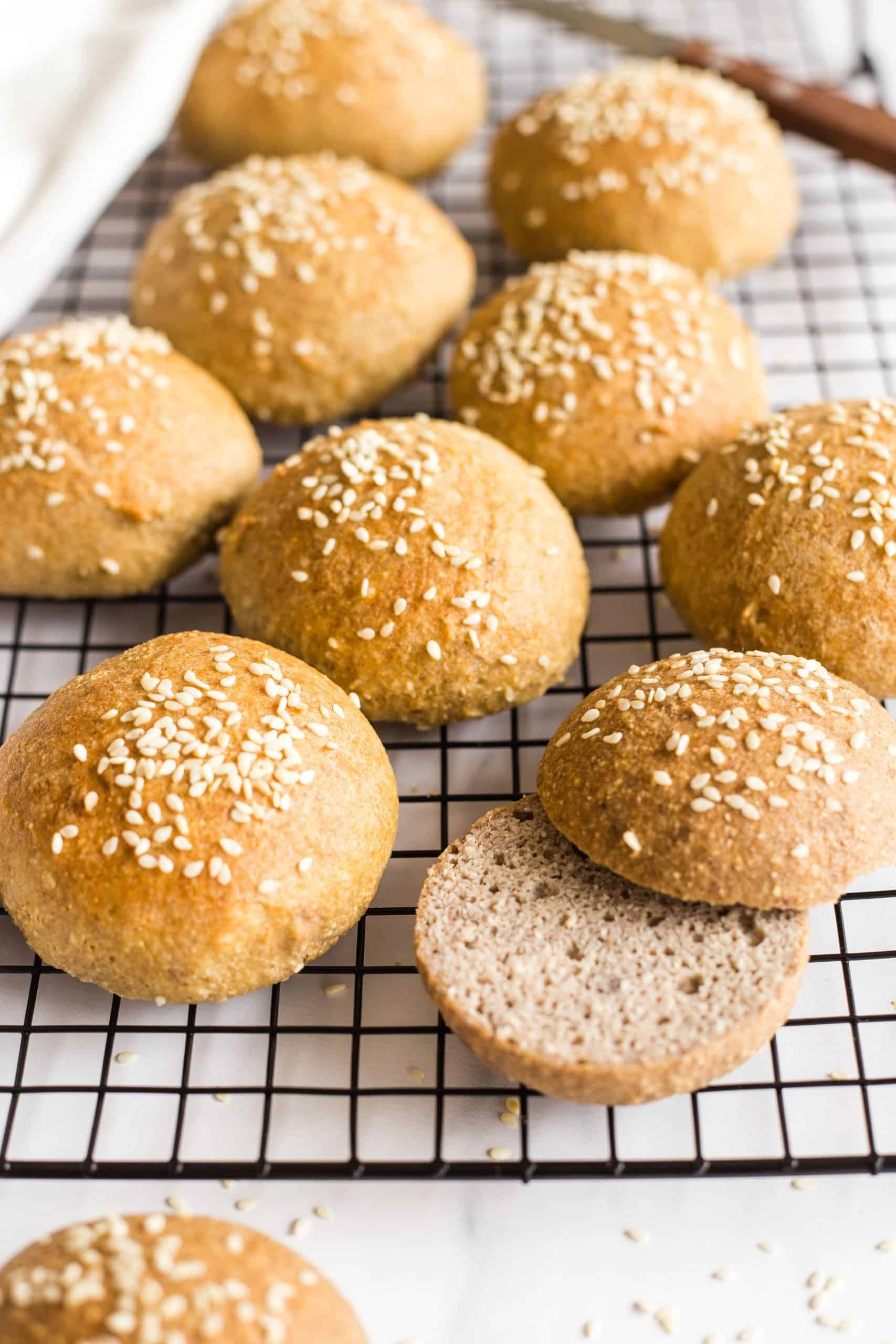 Sliced sesame buns on a cooling rack.