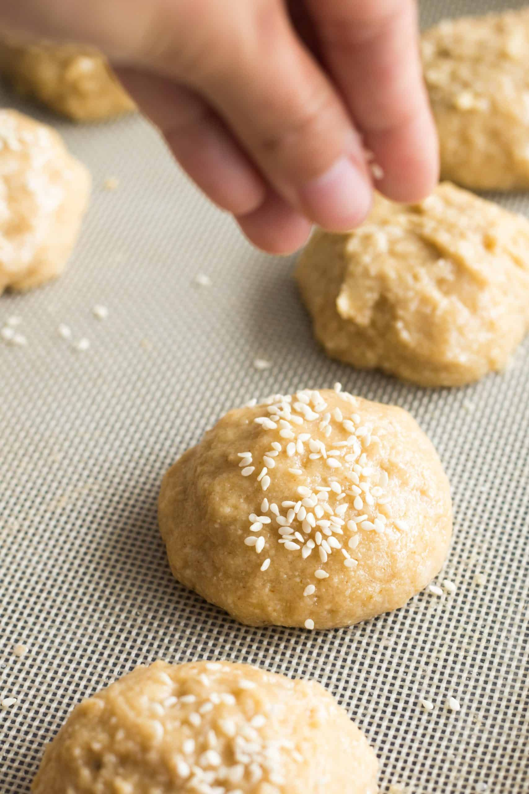 Sprinkling sesame seeds on top of dough balls.