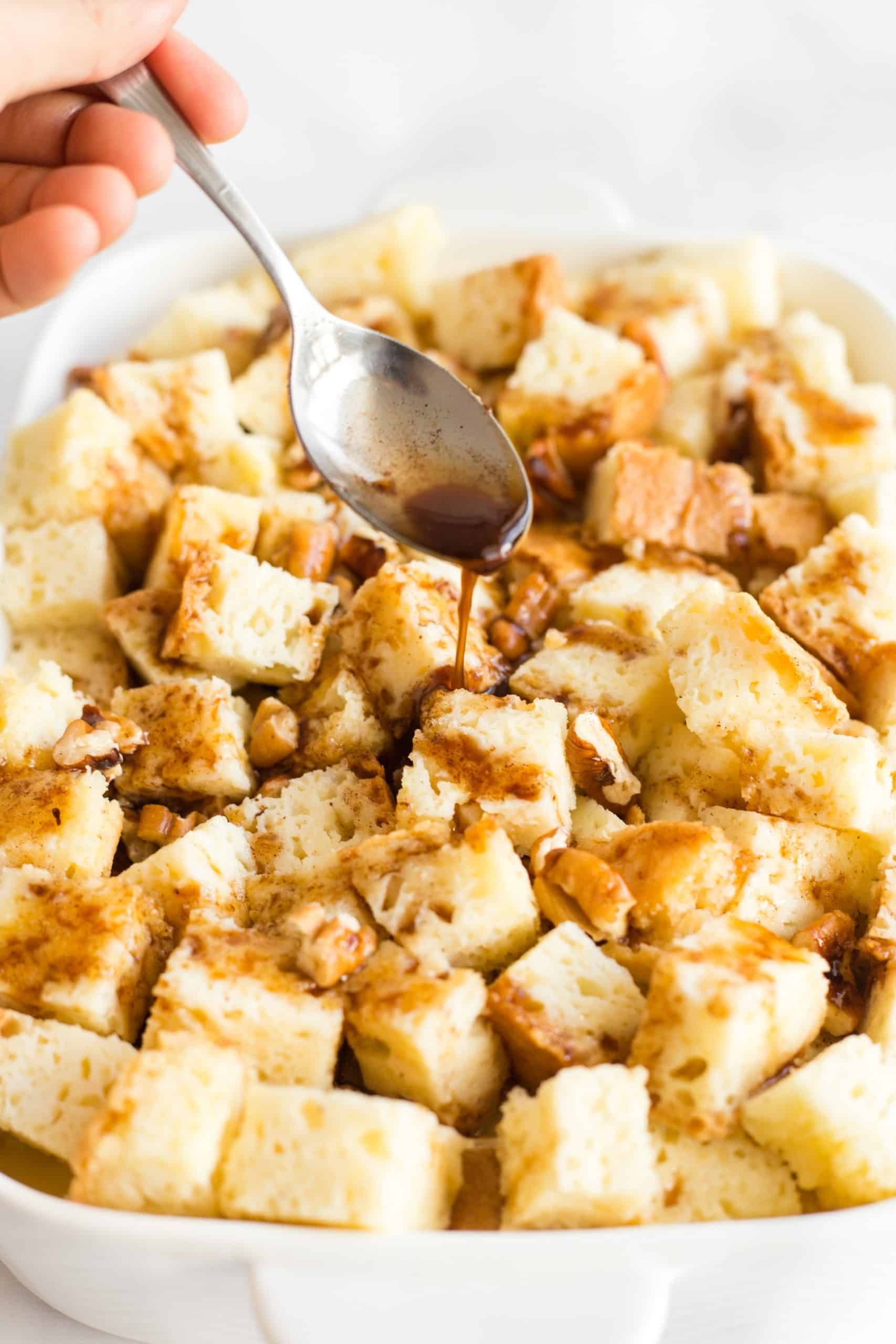 Drizzling cinnamon-sugar topping mixture over bread chunks.