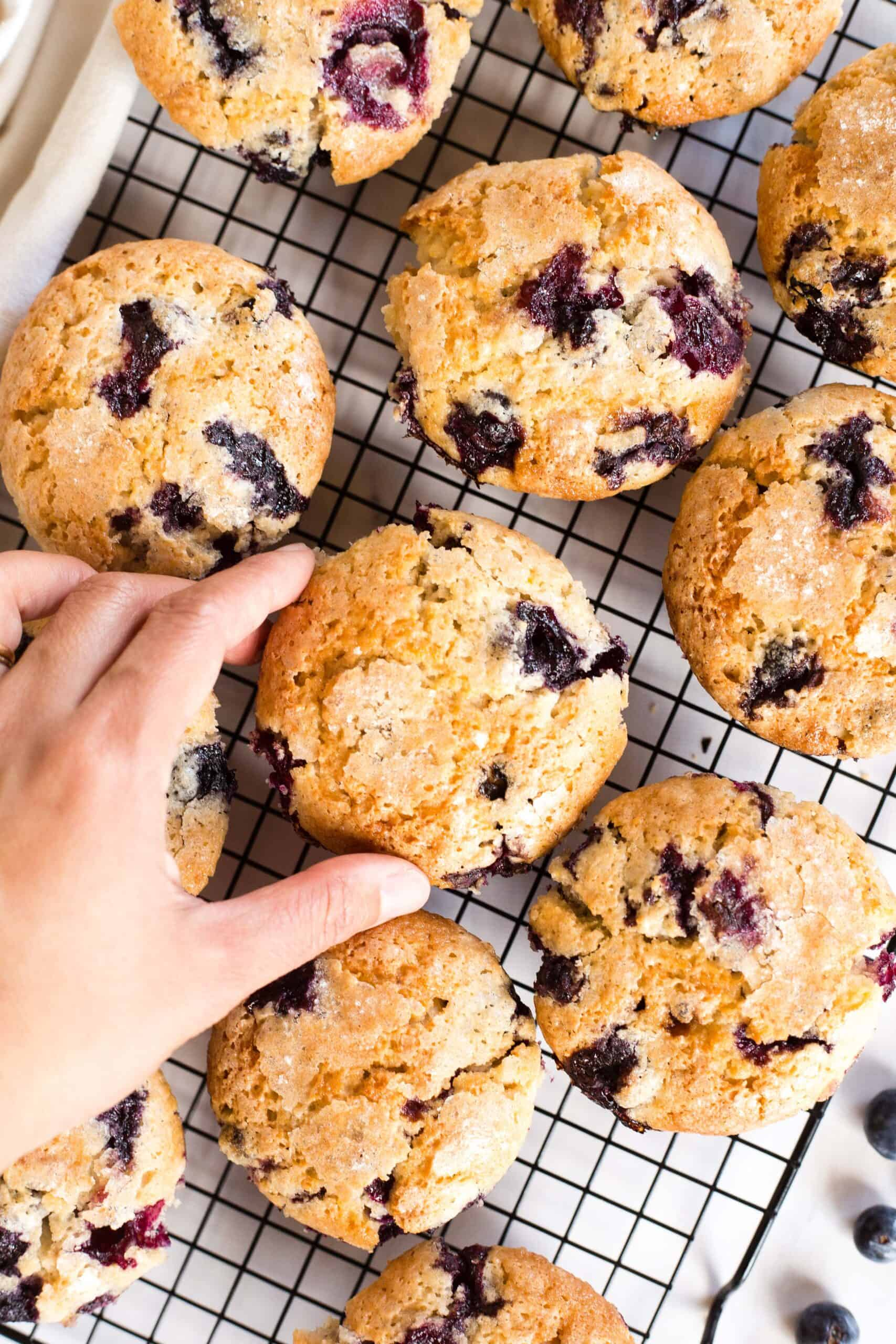 Hand reaching for a muffin from a cooling rack.