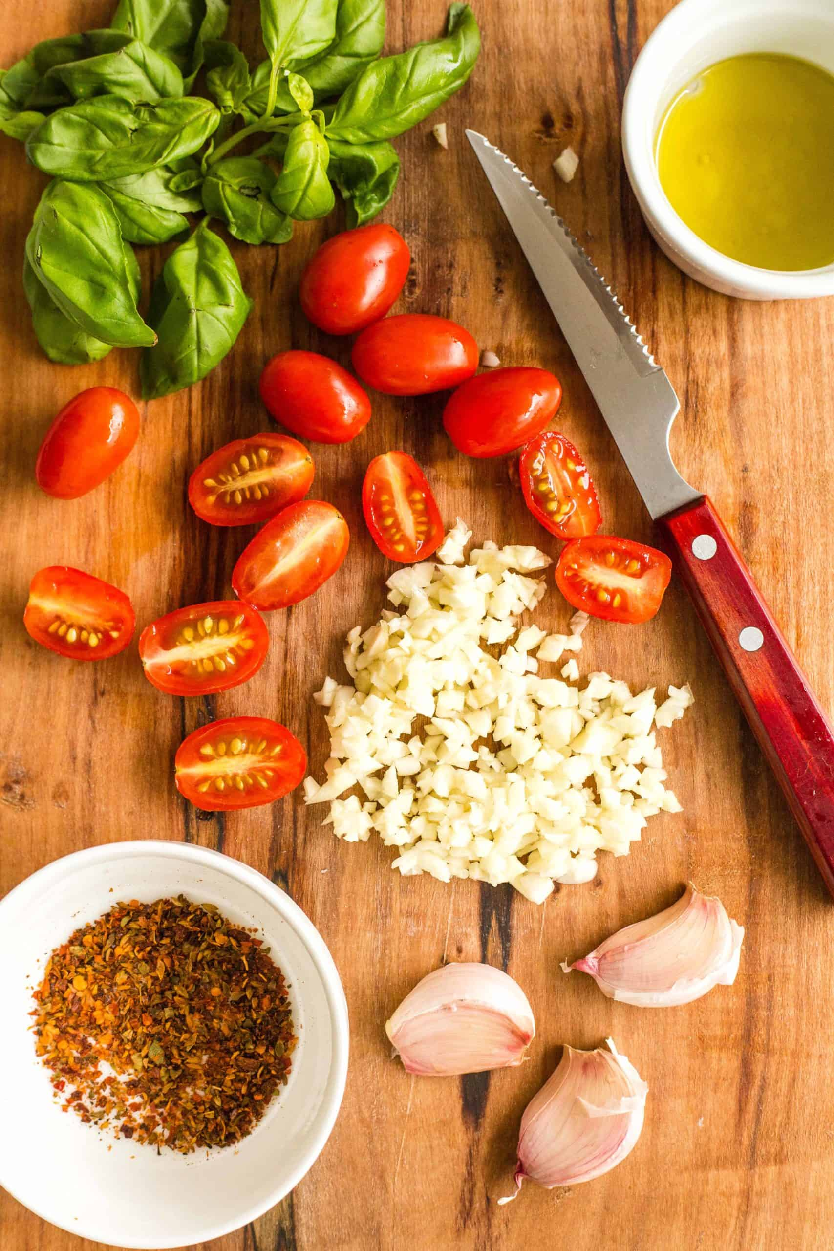 Preparing the topping ingredients for caprese pizza - basil leaves, cherry tomatoes, minced garlic, red chili flakes, olive oil.