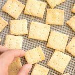 Hand reaching for a cracker on baking sheet