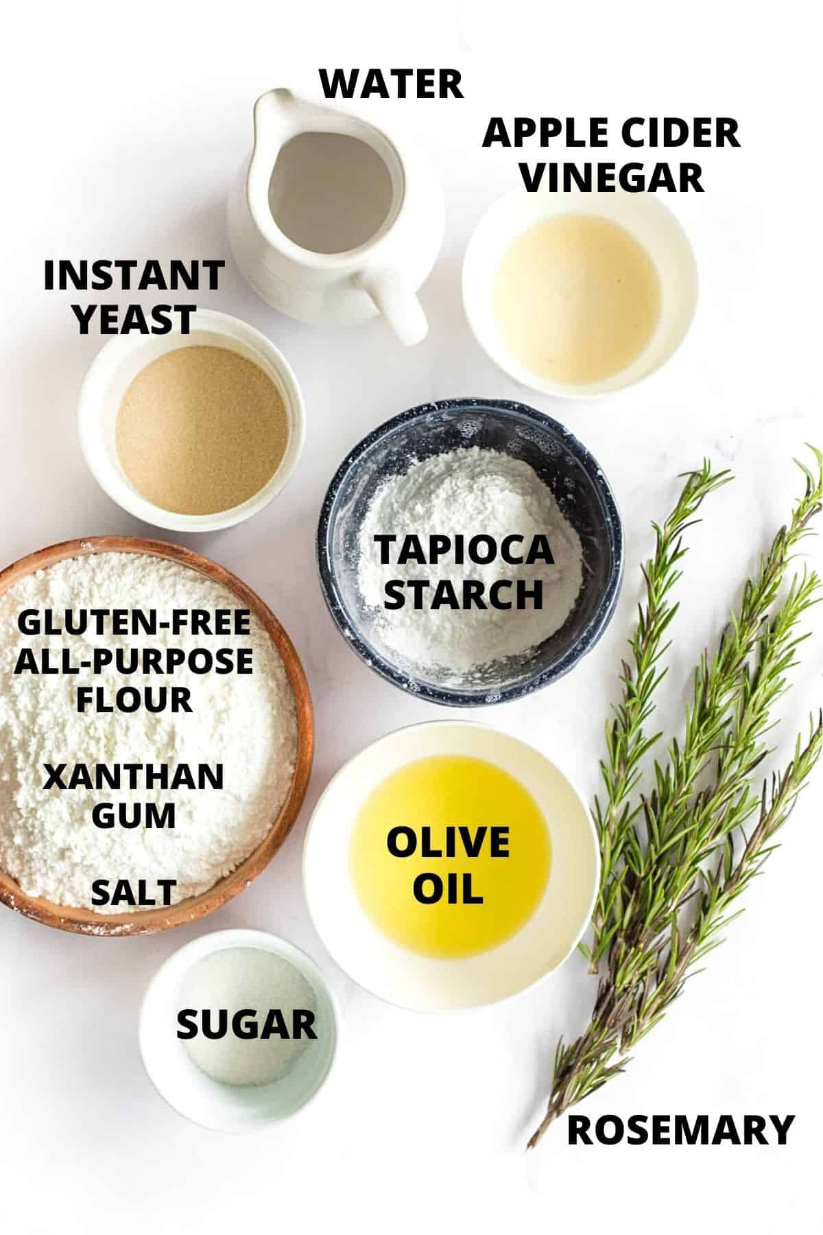 Ingredients for gluten-free focaccia recipe laid out on marble board.