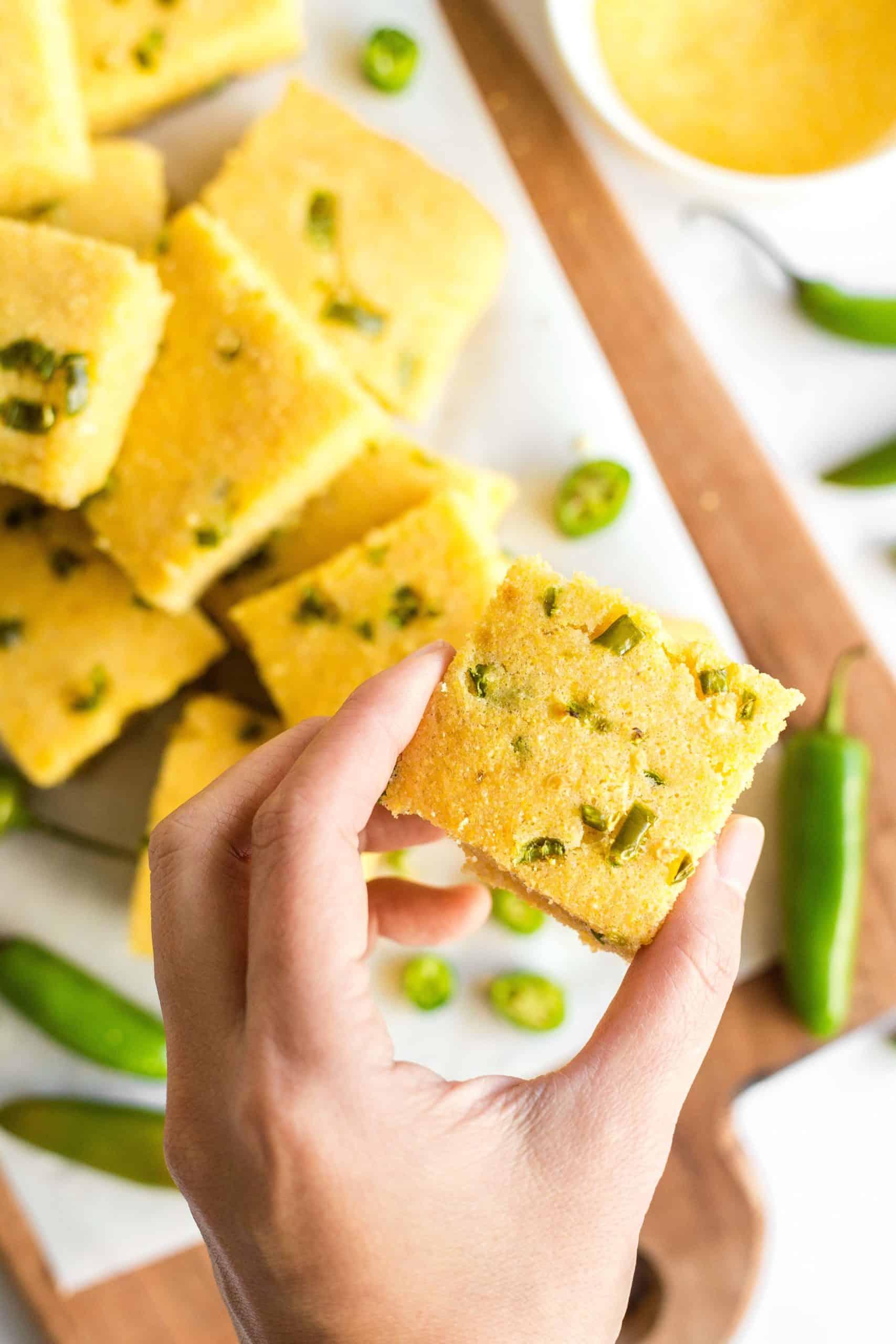 A hand holding up a piece of jalapeño cornbread.