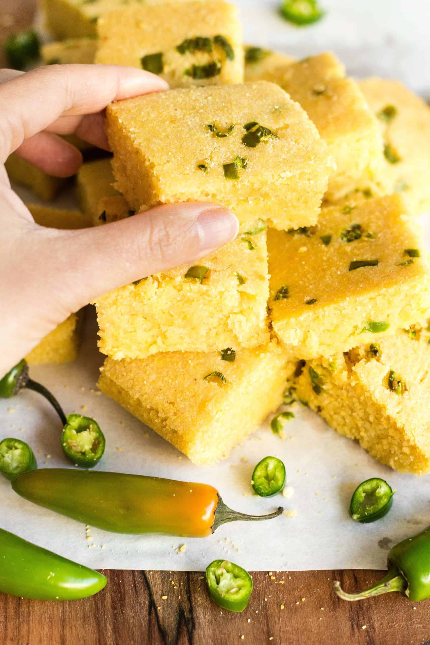 Hand reaching for a piece of jalapeño cornbread.