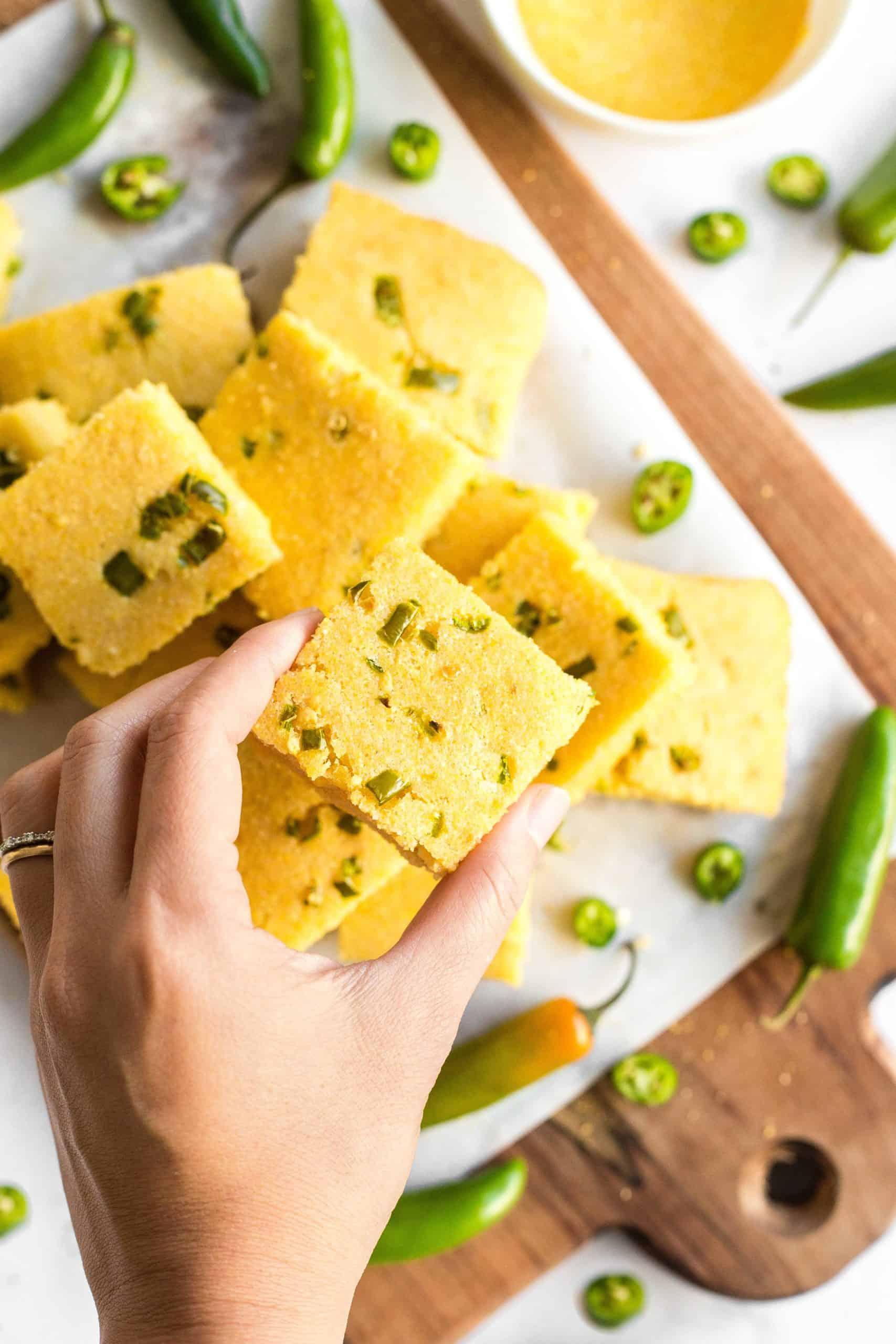 A hand holding up a piece of gluten-free jalapeño cornbread.