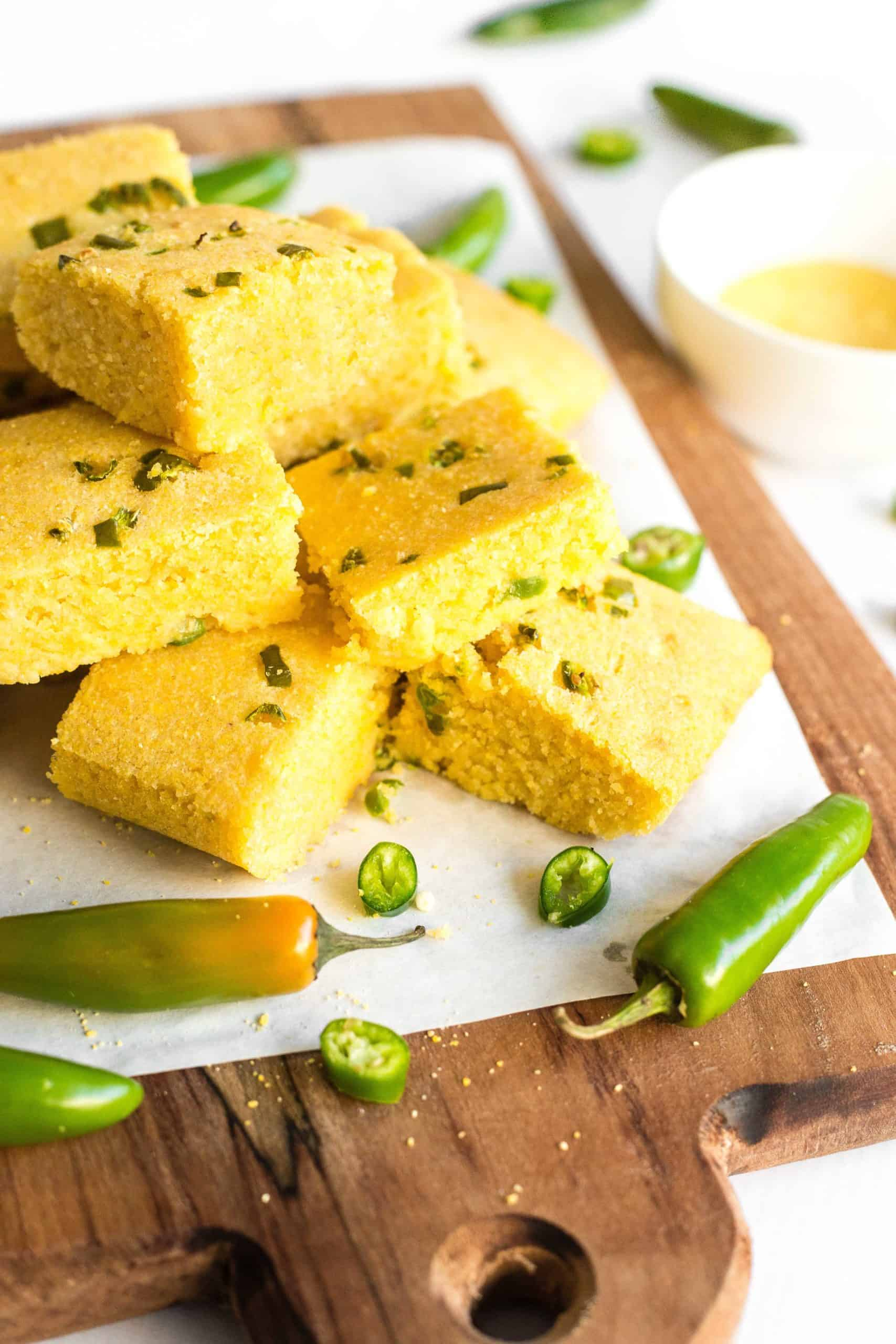 A stack of gluten-free jalapeño cornbread squares and fresh jalapeño peppers on a parchment-lined wooden board.