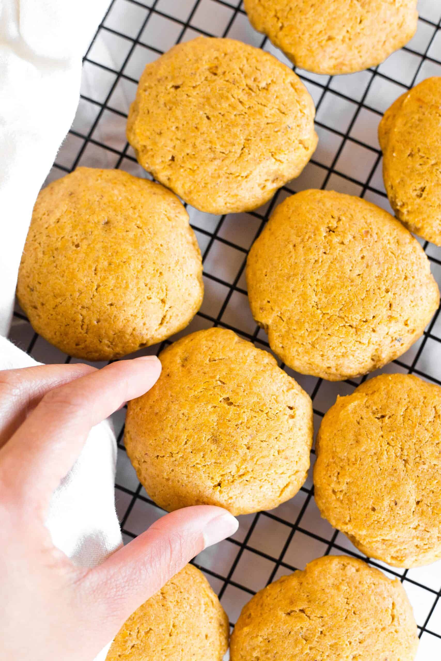 Reaching for a pumpkin cookie on a cooling rack.