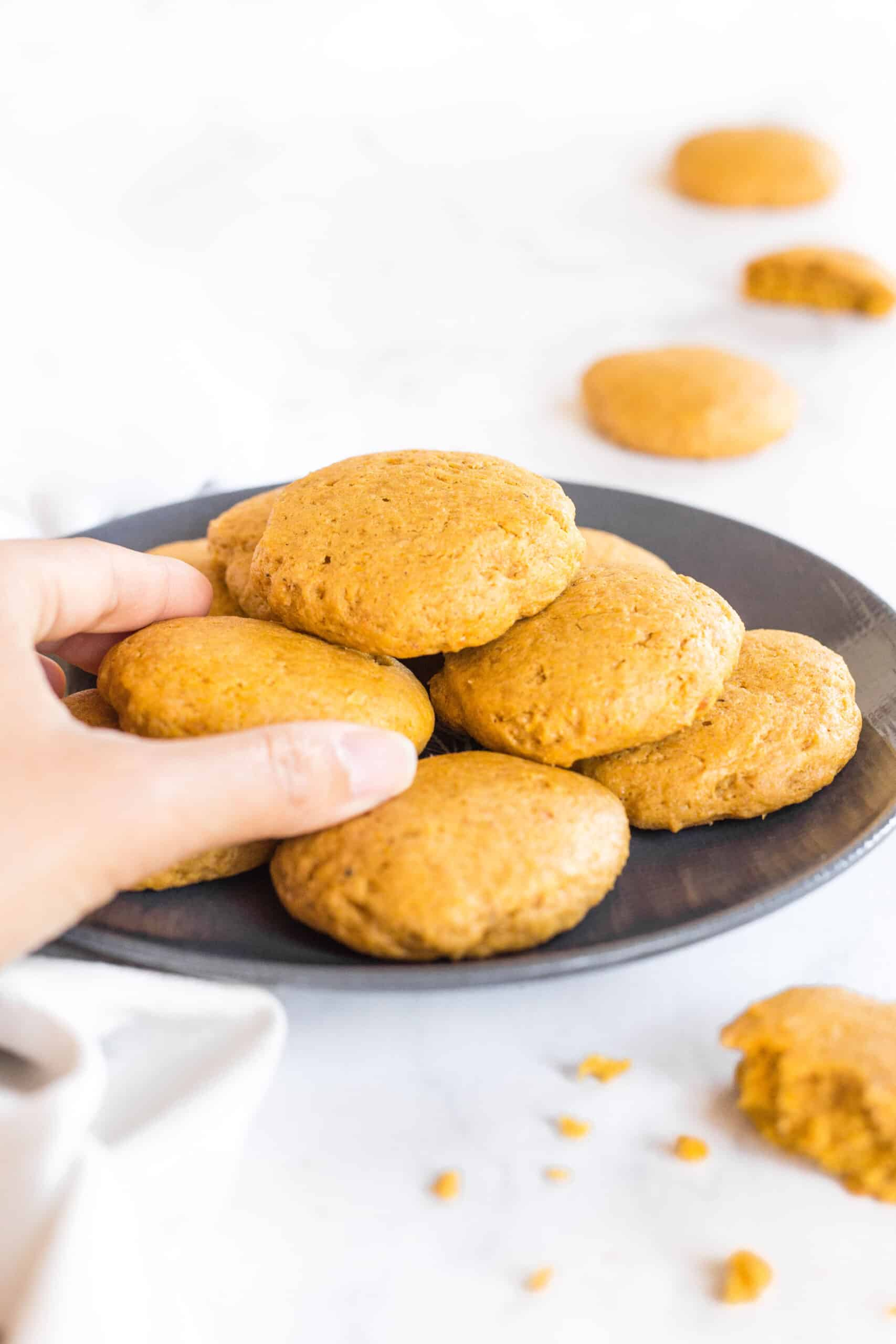 Hand reaching for a cookie from a plate filled with pumpkin cookies.