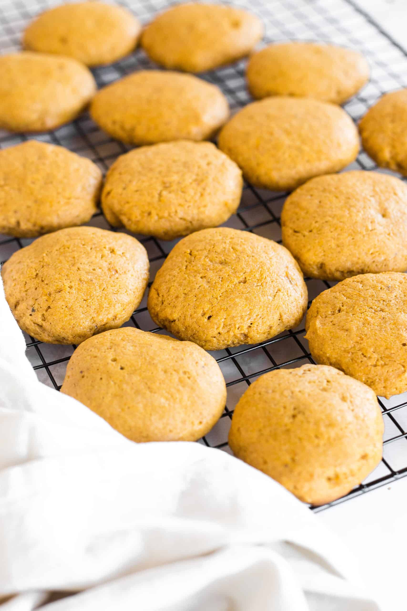 Soft pumpkin cookies on a wire rack with a kitchen towel.