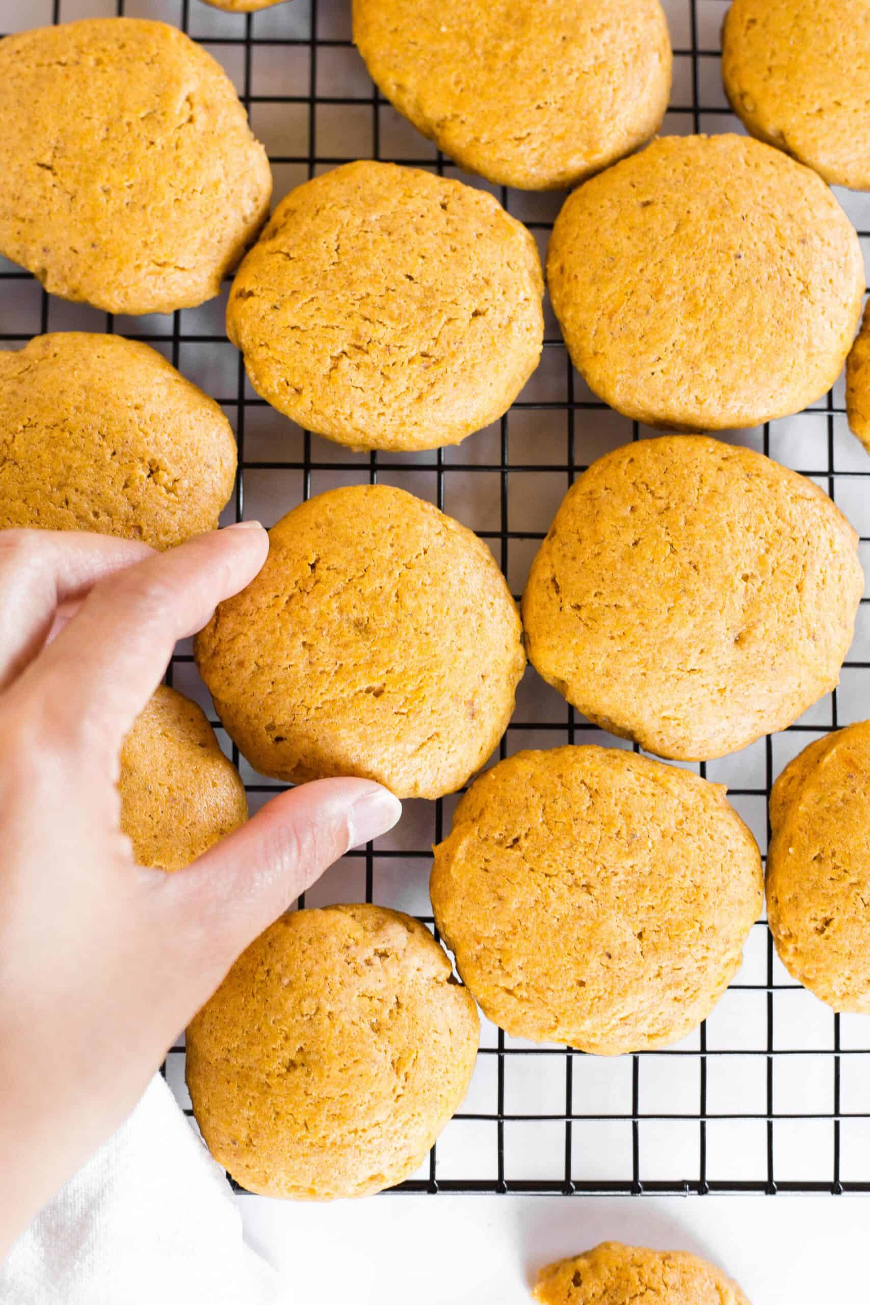 Hand reaching for gluten-free pumpkin cookies on a wire rack.