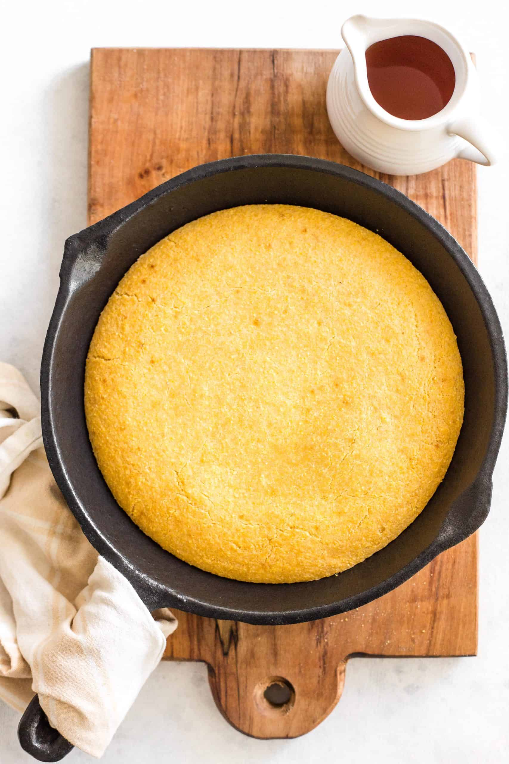 A skillet with cornbread on a wooden board.