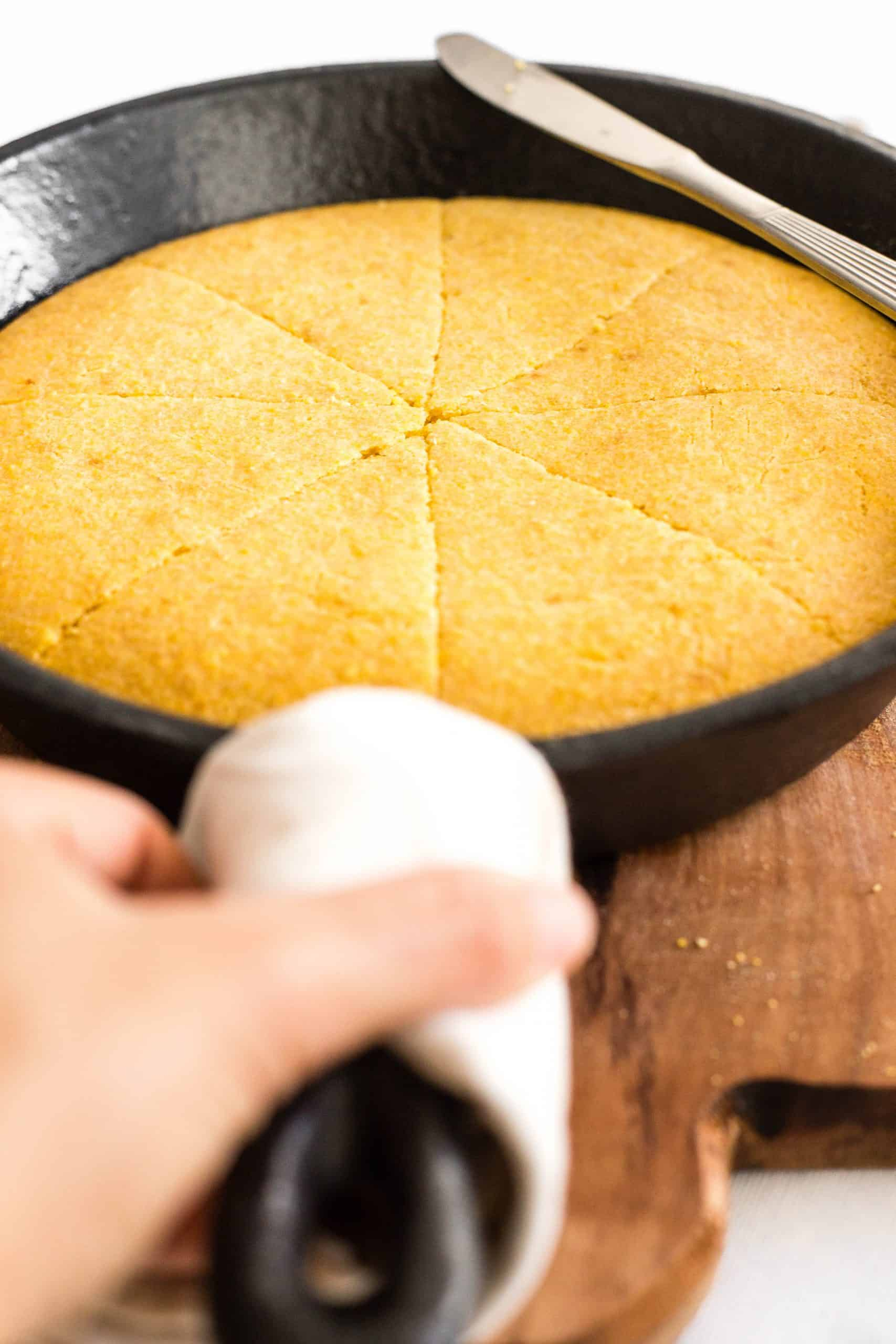 Hand reaching for a skillet with gluten-free cornbread.