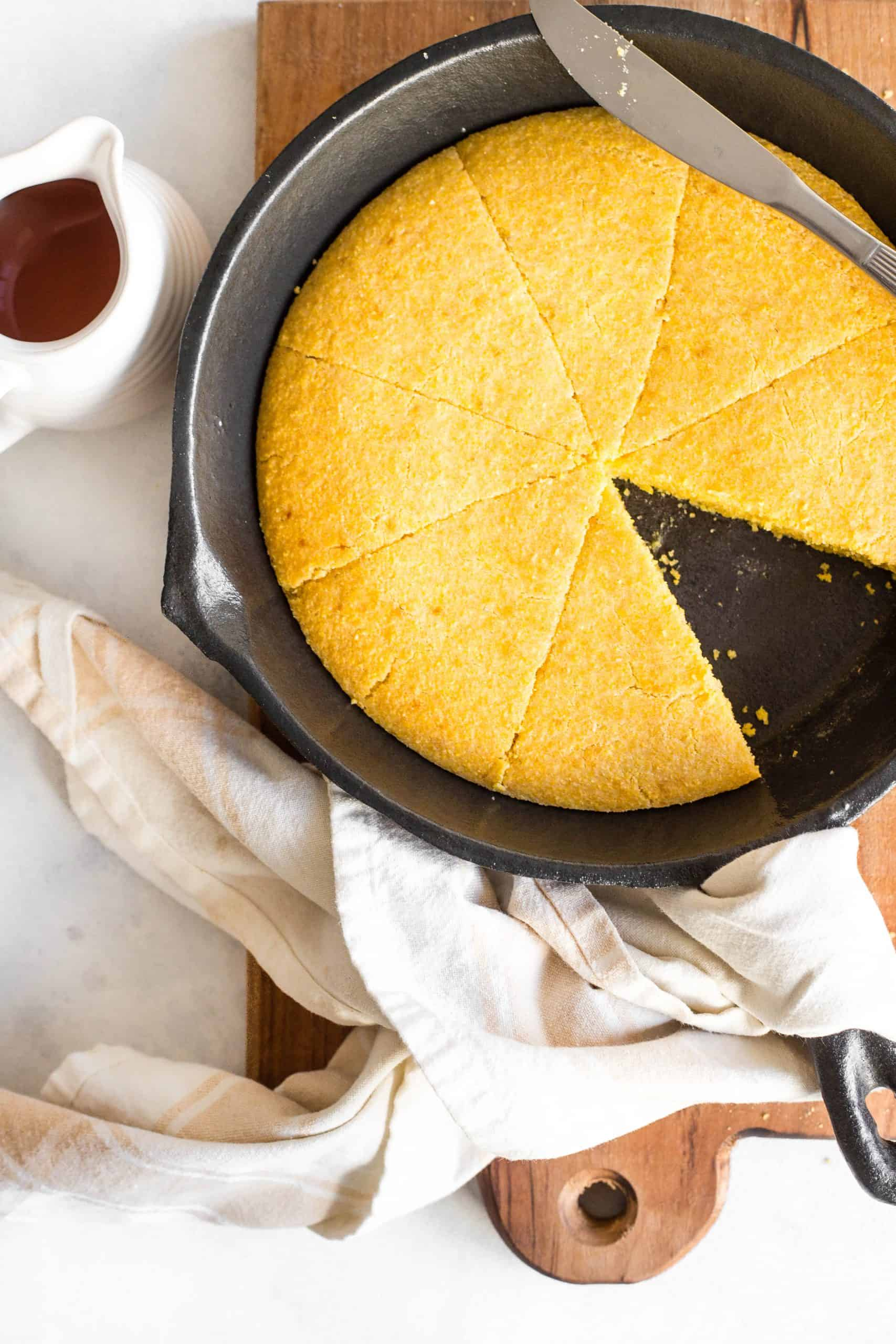 Top down view of a skillet with cornbread and a small jug of honey.
