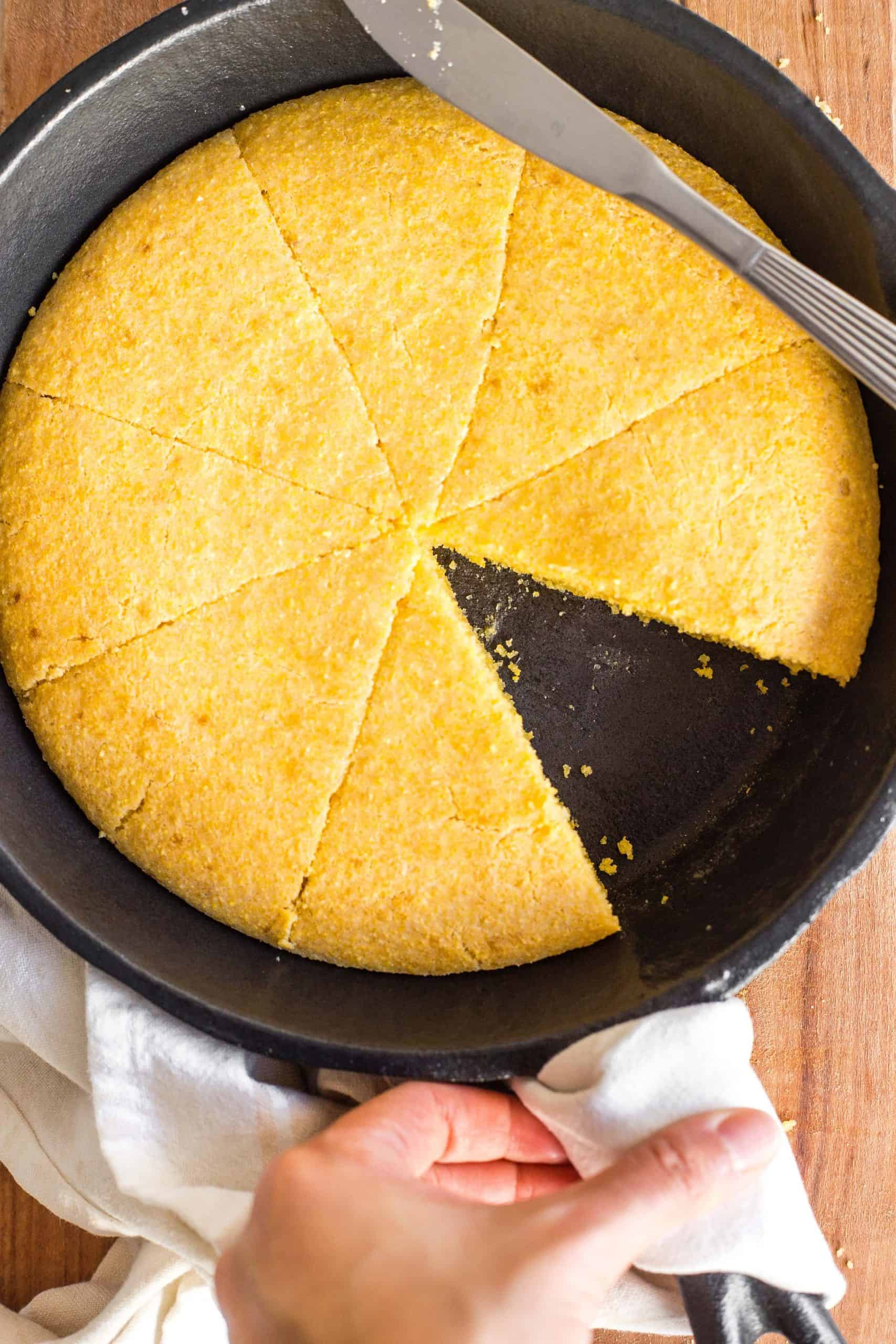 Sliced cornbread in a cast iron skillet.