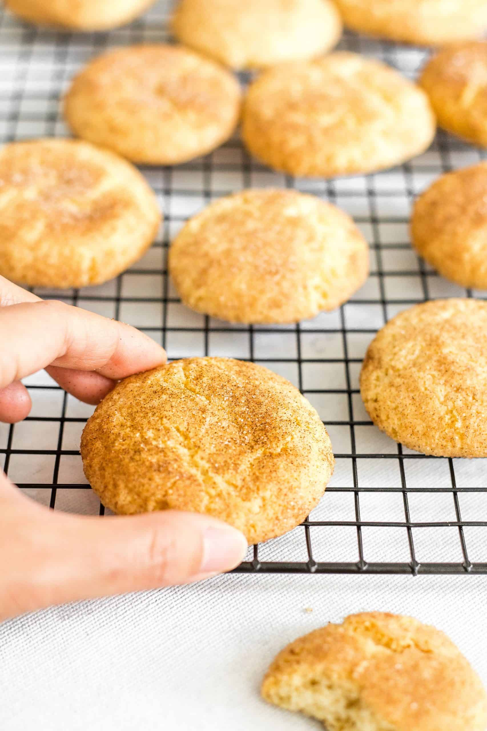 Reaching for a snickerdoodle cookie on a cooling rack.