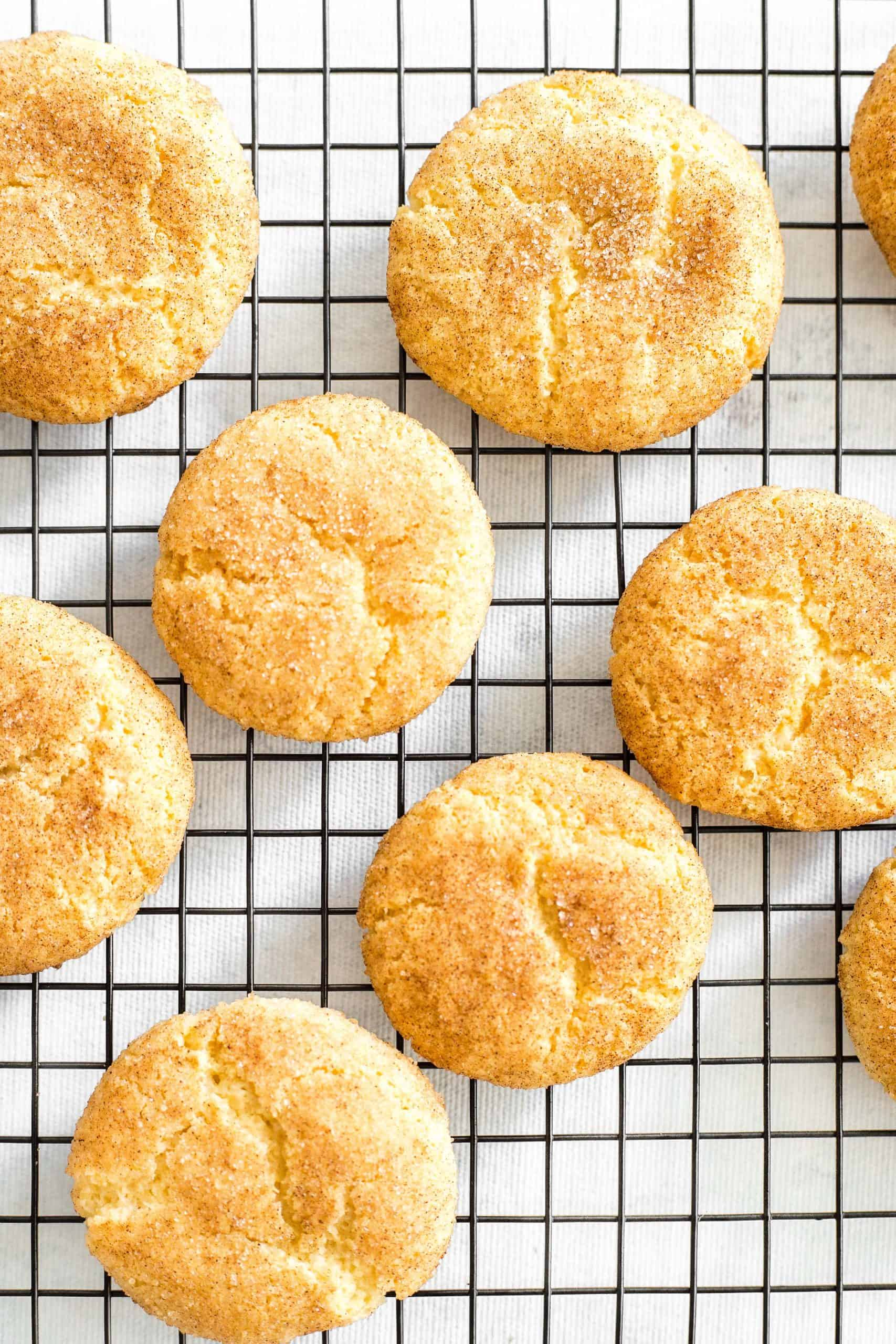 Snickerdoodle cookies cooling on a wire rack.