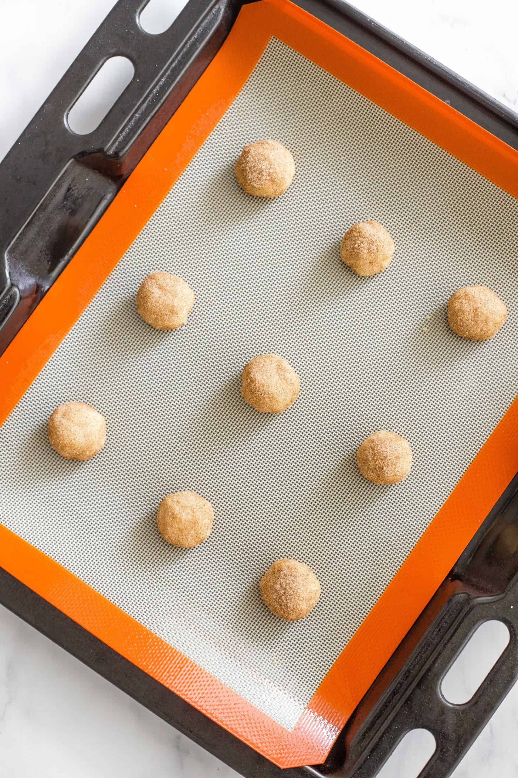 Cookie dough balls on a silpat-lined baking sheet.