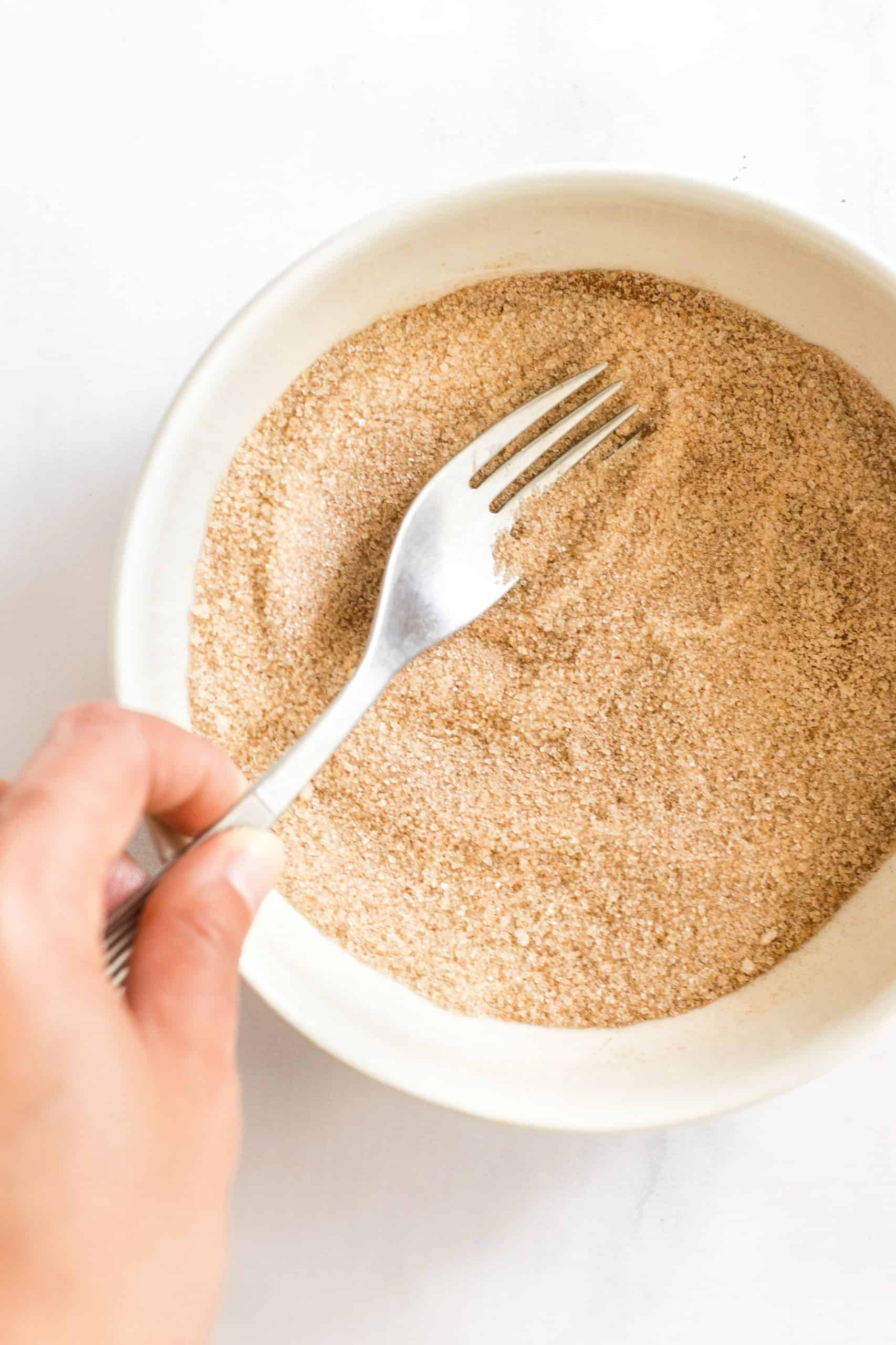 Fork mixing cinnamon sugar mixture in a white bowl.