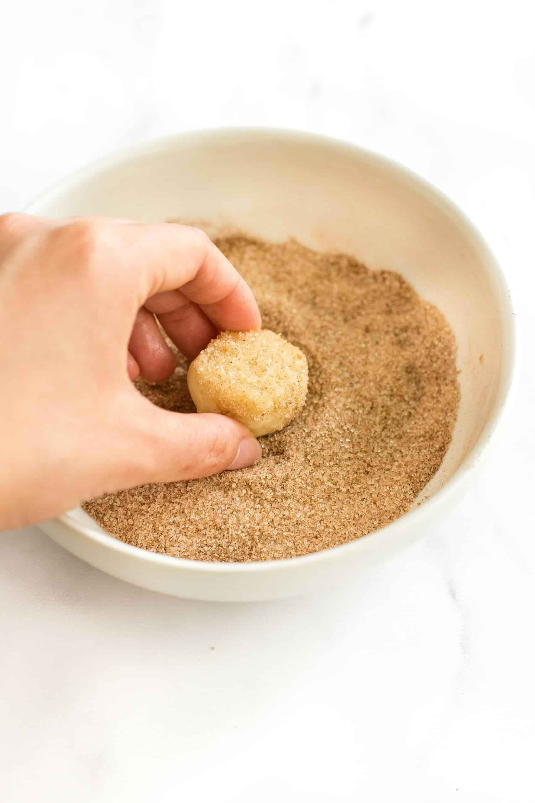 Rolling cookie dough ball in a cinnamon sugar mixture.