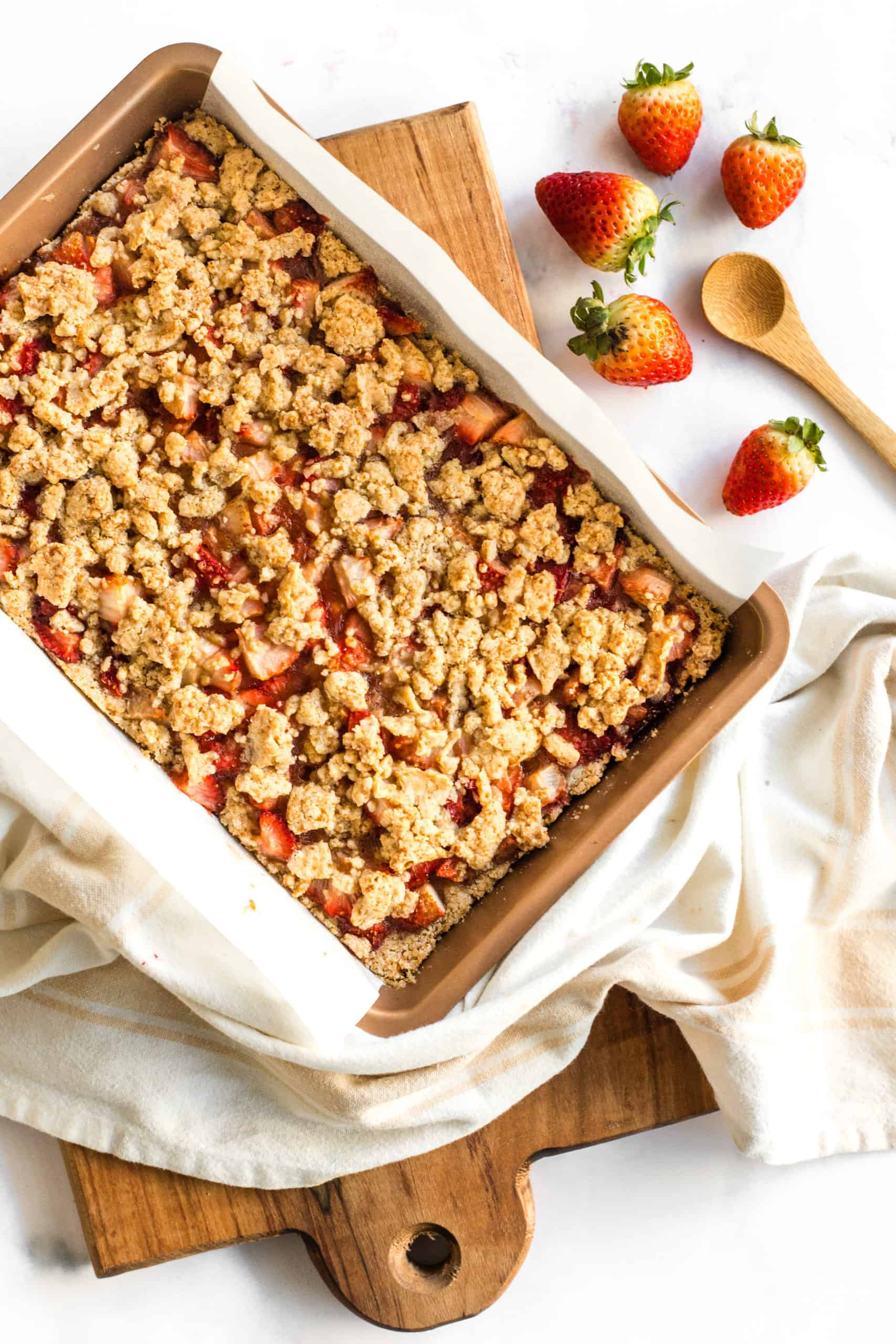 Gluten-free strawberry crumb bars just baked still in a pan and cooling on a wooden board.