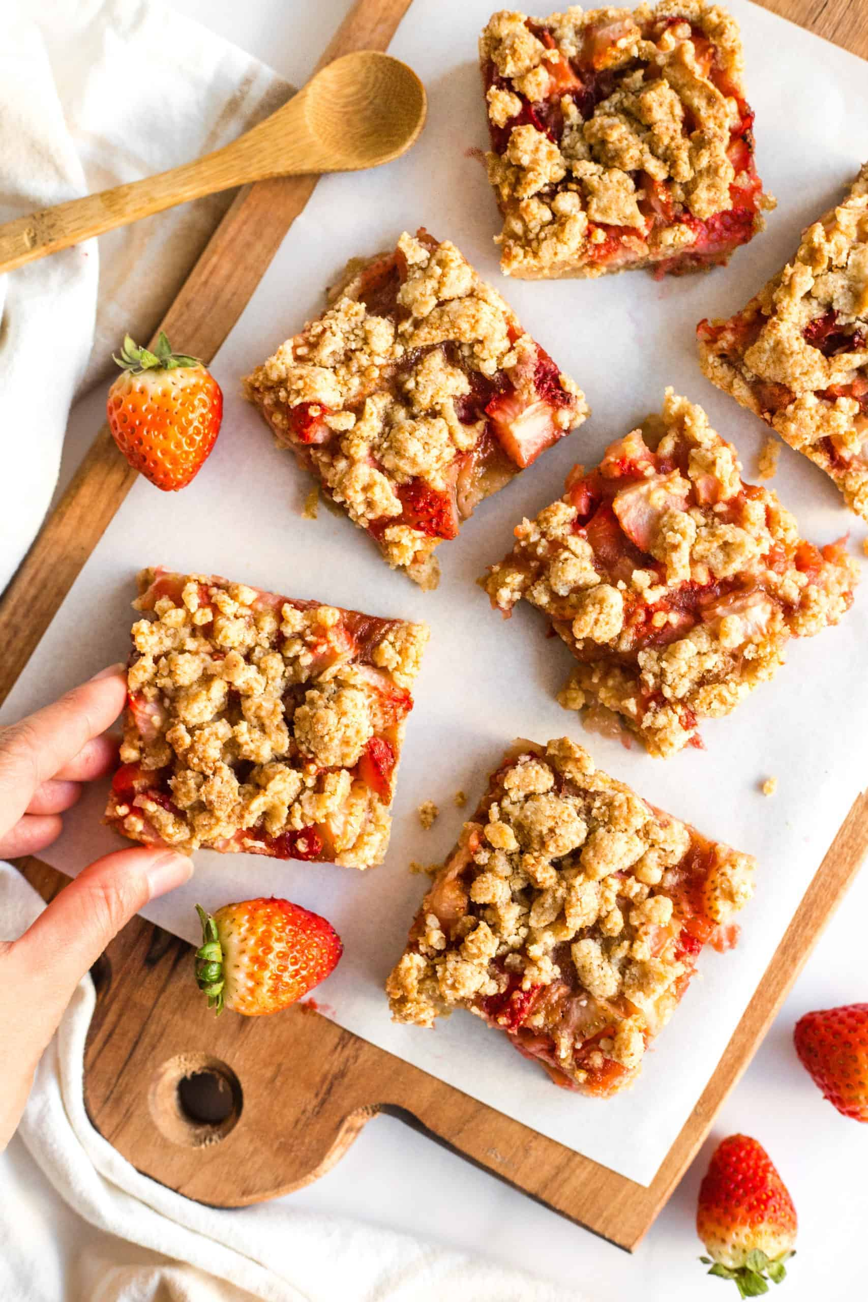 Gluten-Free Strawberry Crumb Bars on a parchment-lined wooden board.