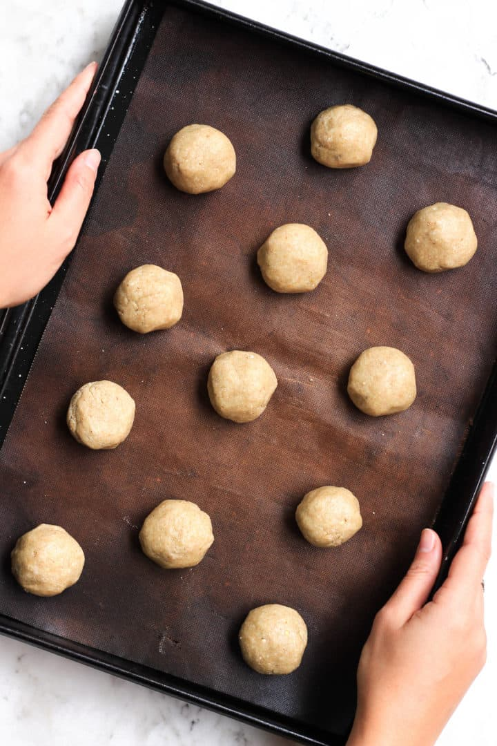 Round balls of cookie dough spread out on a cookie sheet.