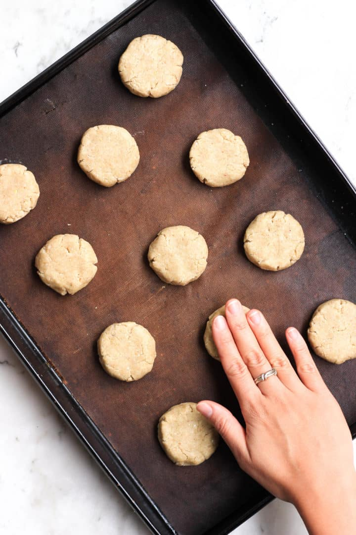 Flattening cookie dough on a cookie sheet.
