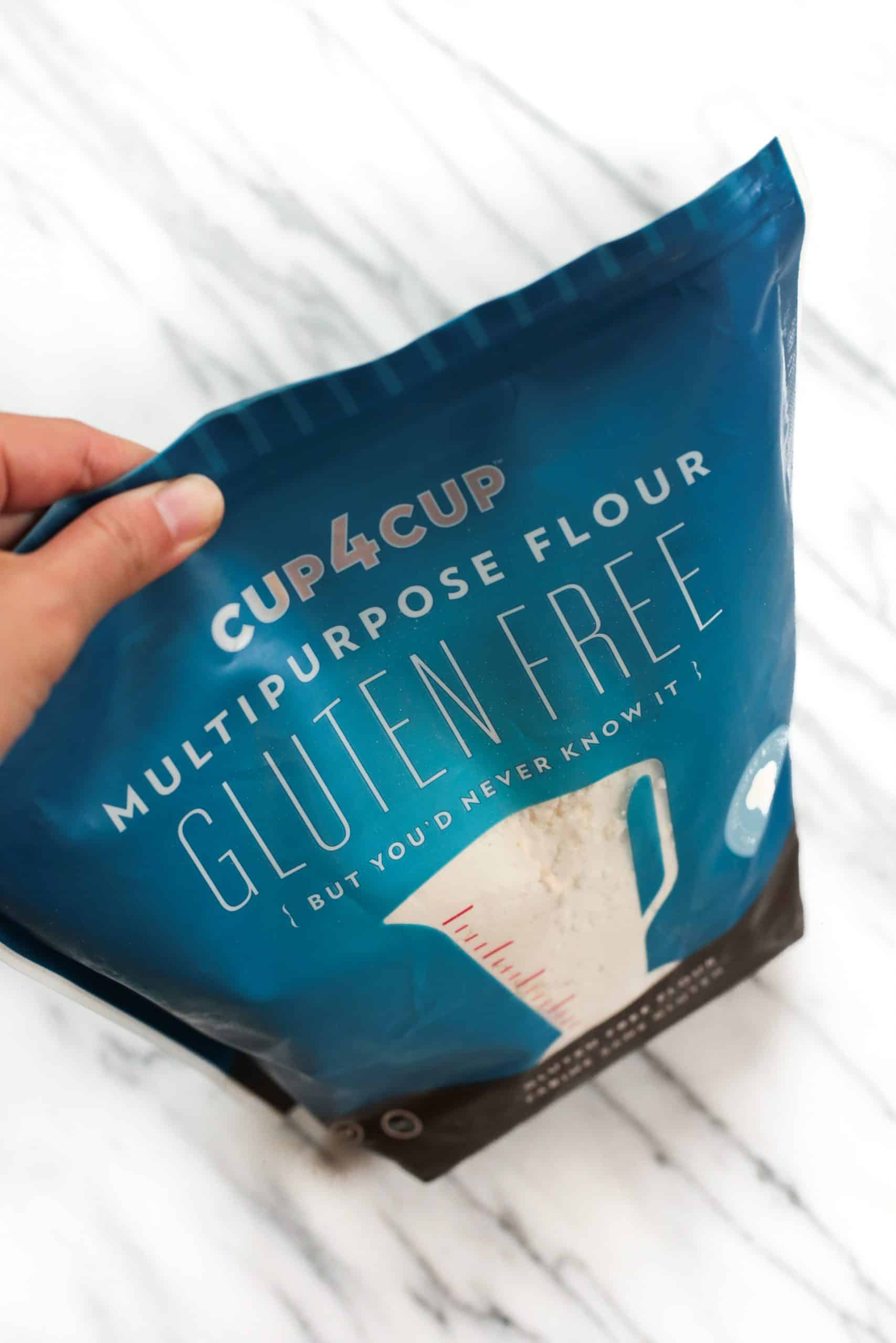 Hand holding a bag of Cup4Cup flour.